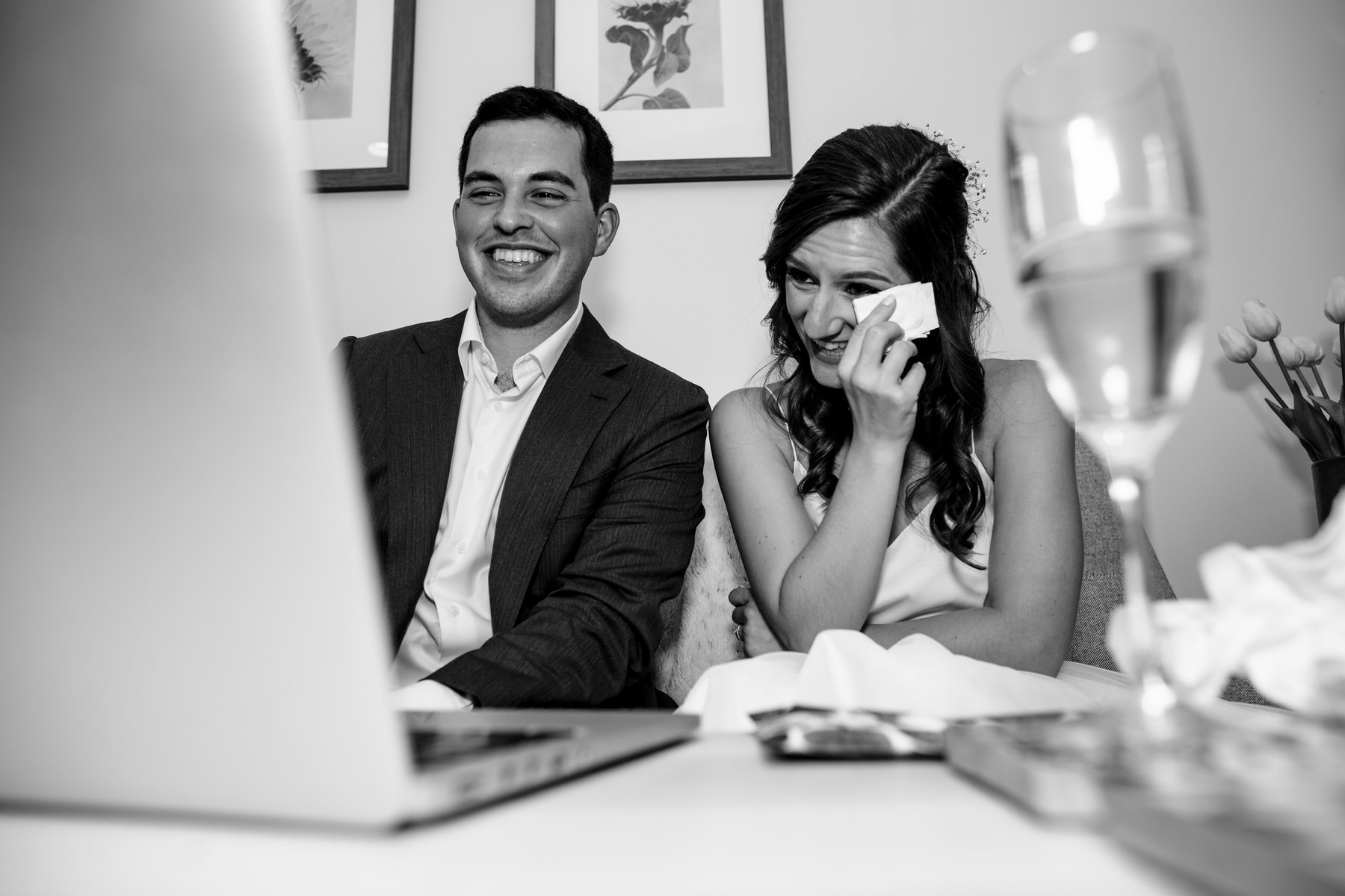 Washington D.C. Wedding Photo of Cocktail Hour | The bride and the groom are watching a video of the friends and family