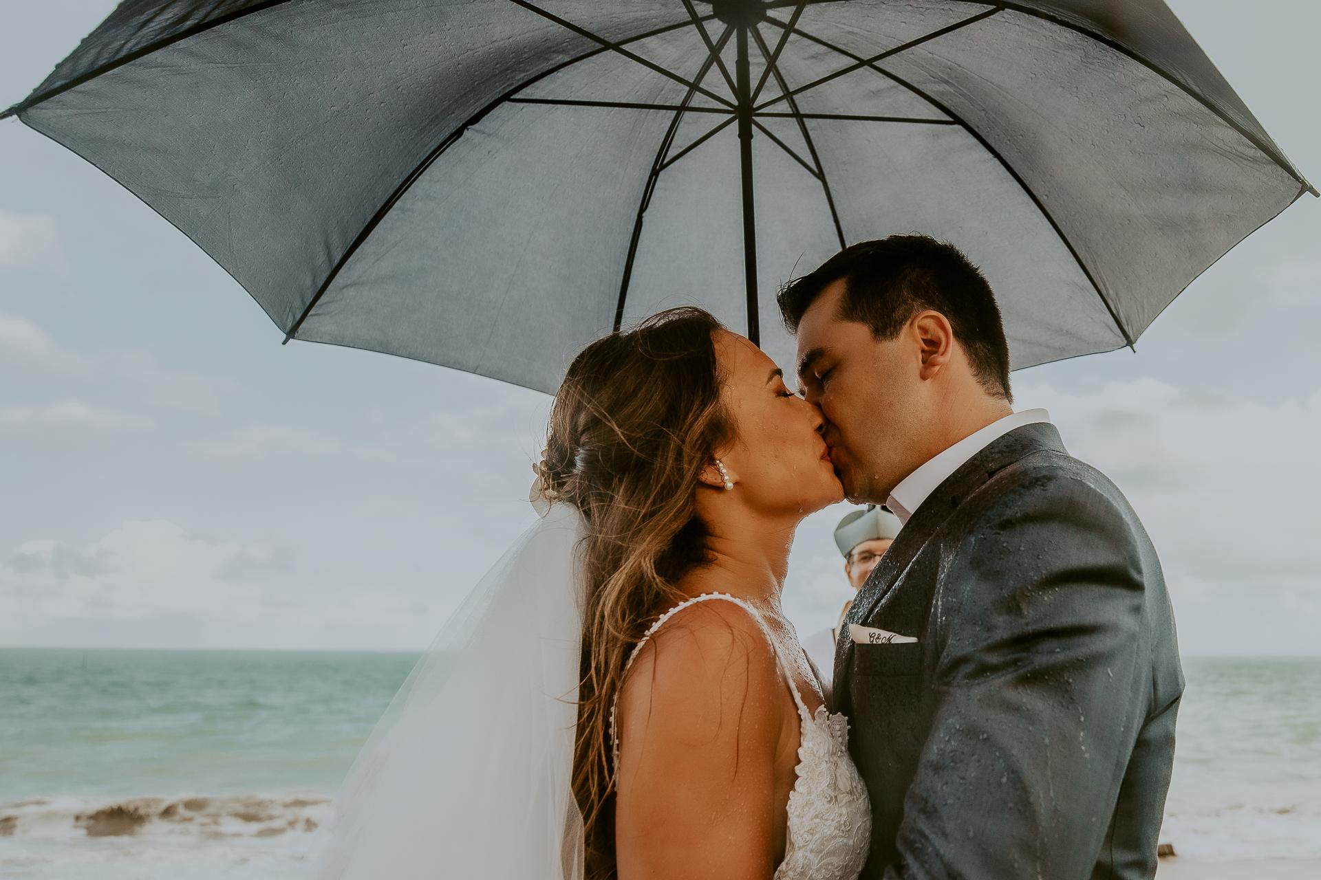 Porto de Pedras beach wedding image | Seeking shelter under an umbrella