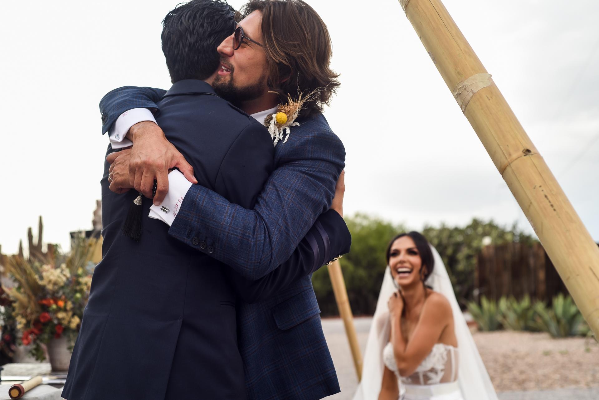 Photographie de mariage à San Miguel de Allende | Le marié embrasse son témoin après avoir terminé son discours émouvant et édifiant