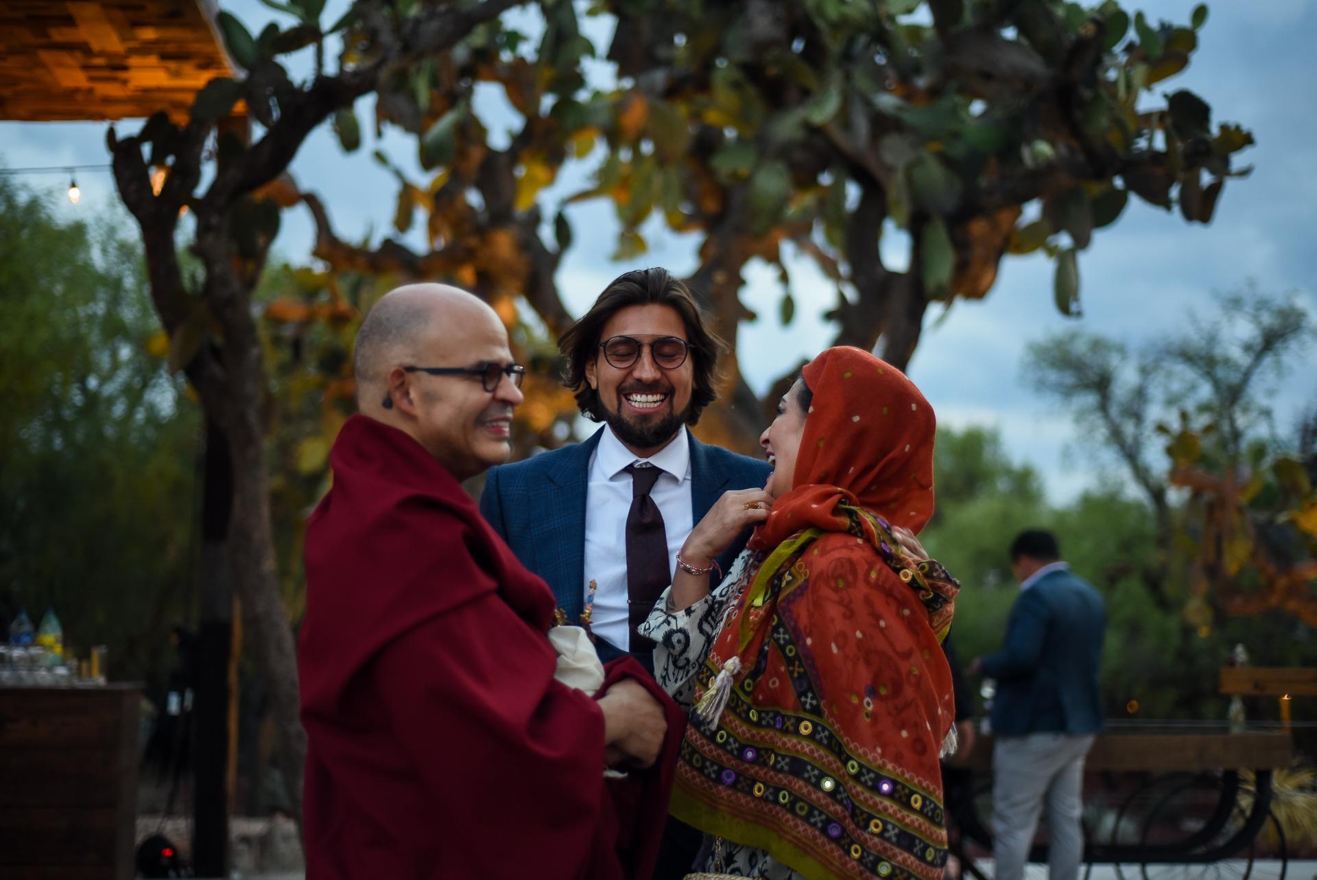 Photographes pour San Miguel de Allende | Le marié sourit lors d'une conversation avec deux invités spéciaux