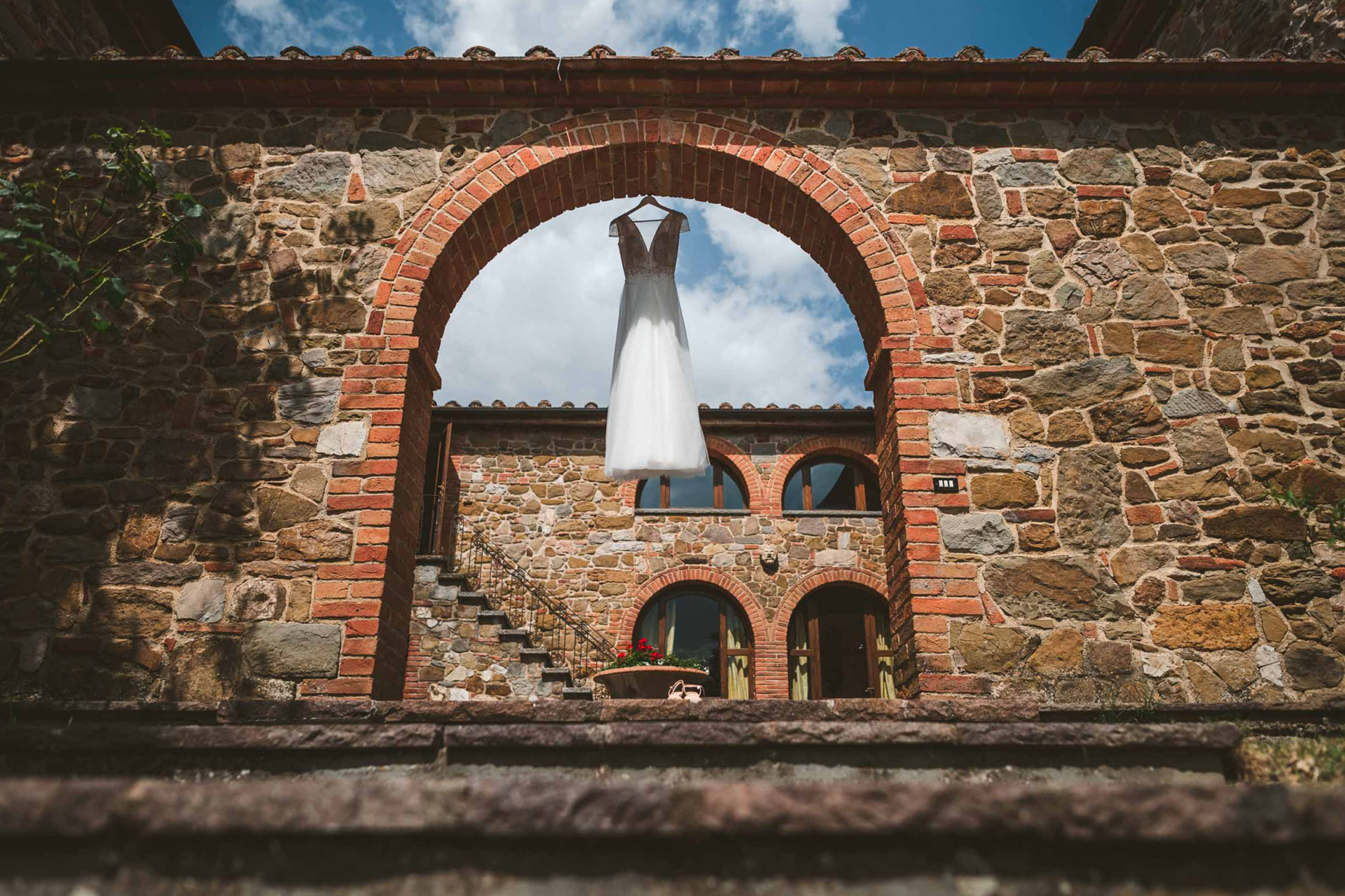 Photo de détail de mariage en Toscane - Sinalunga, Sienne | La robe est suspendue dans la cour