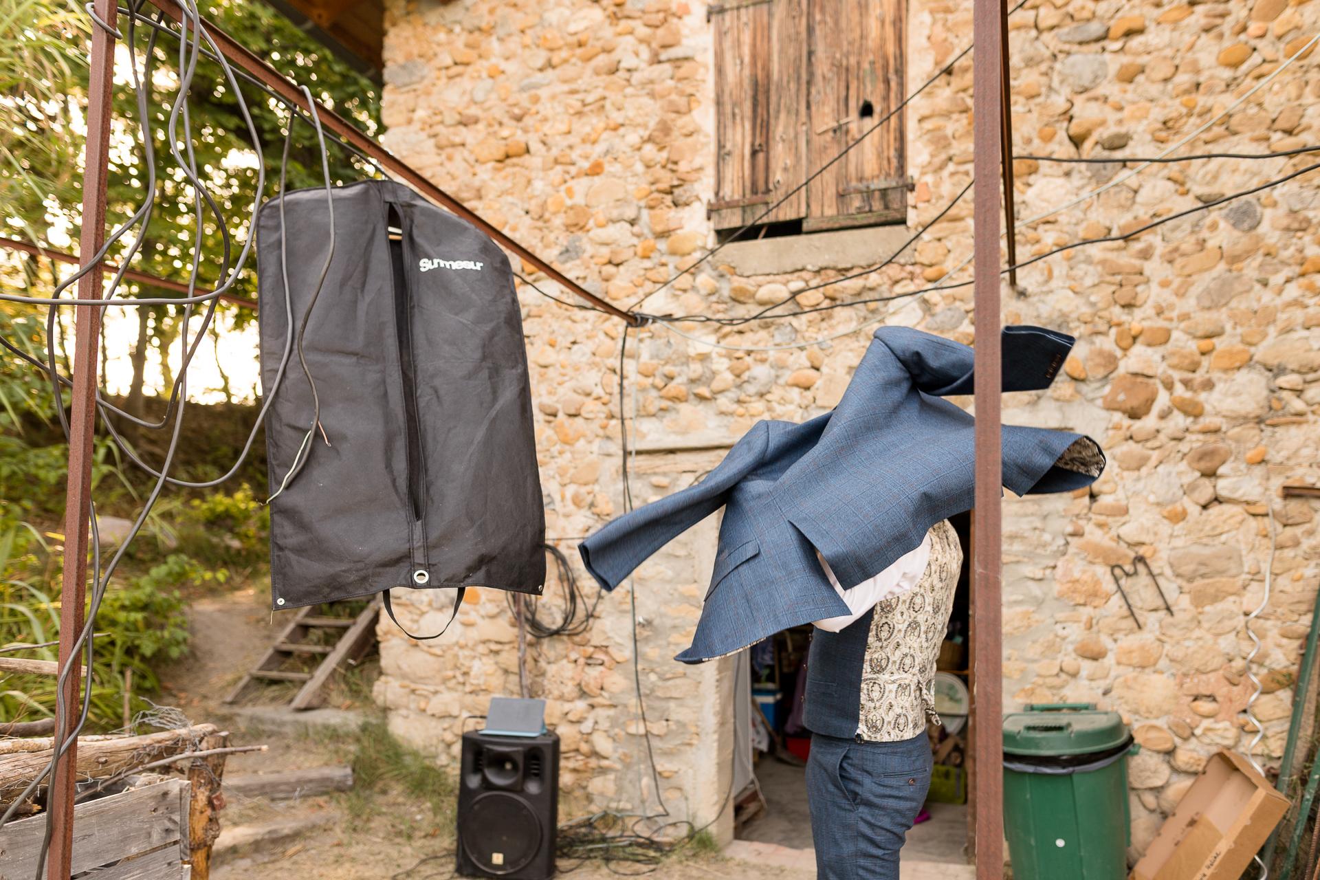 Fotógrafo Mezel para Bodas en Francia | El novio está sacando el abrigo de su traje de una bolsa de ropa