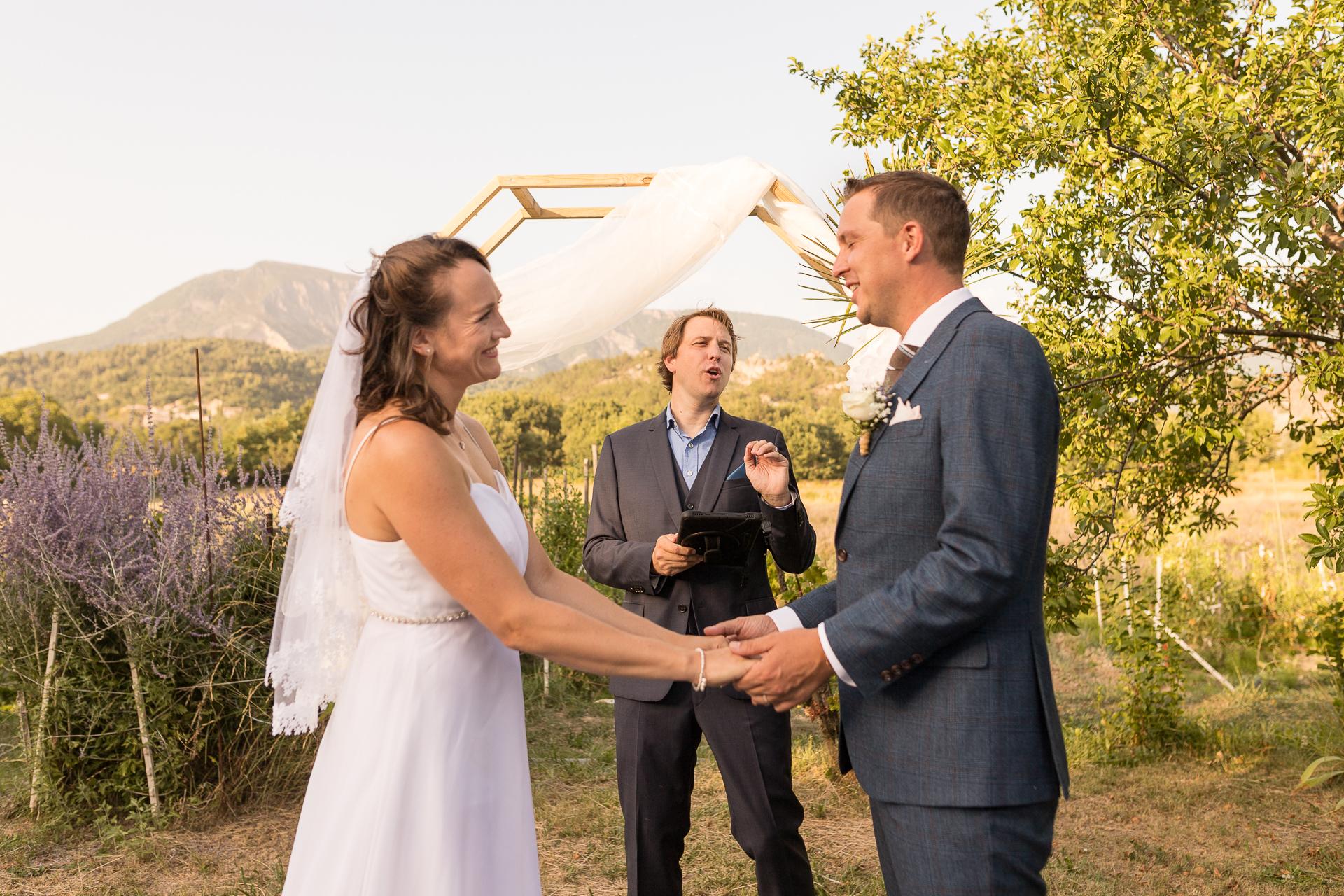 Mézel - Fotografía de la ceremonia de boda de Francia | La pareja se toma de la mano y se miran a los ojos.