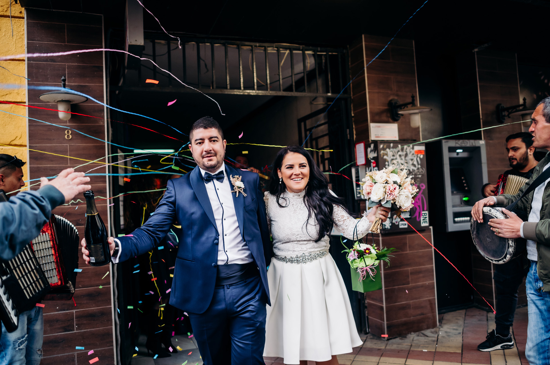 Sofia, Bulgaria Destination Wedding Photographer | Leaving the civil marriage hall carrying a bottle of champagne and a bouquet of flowers