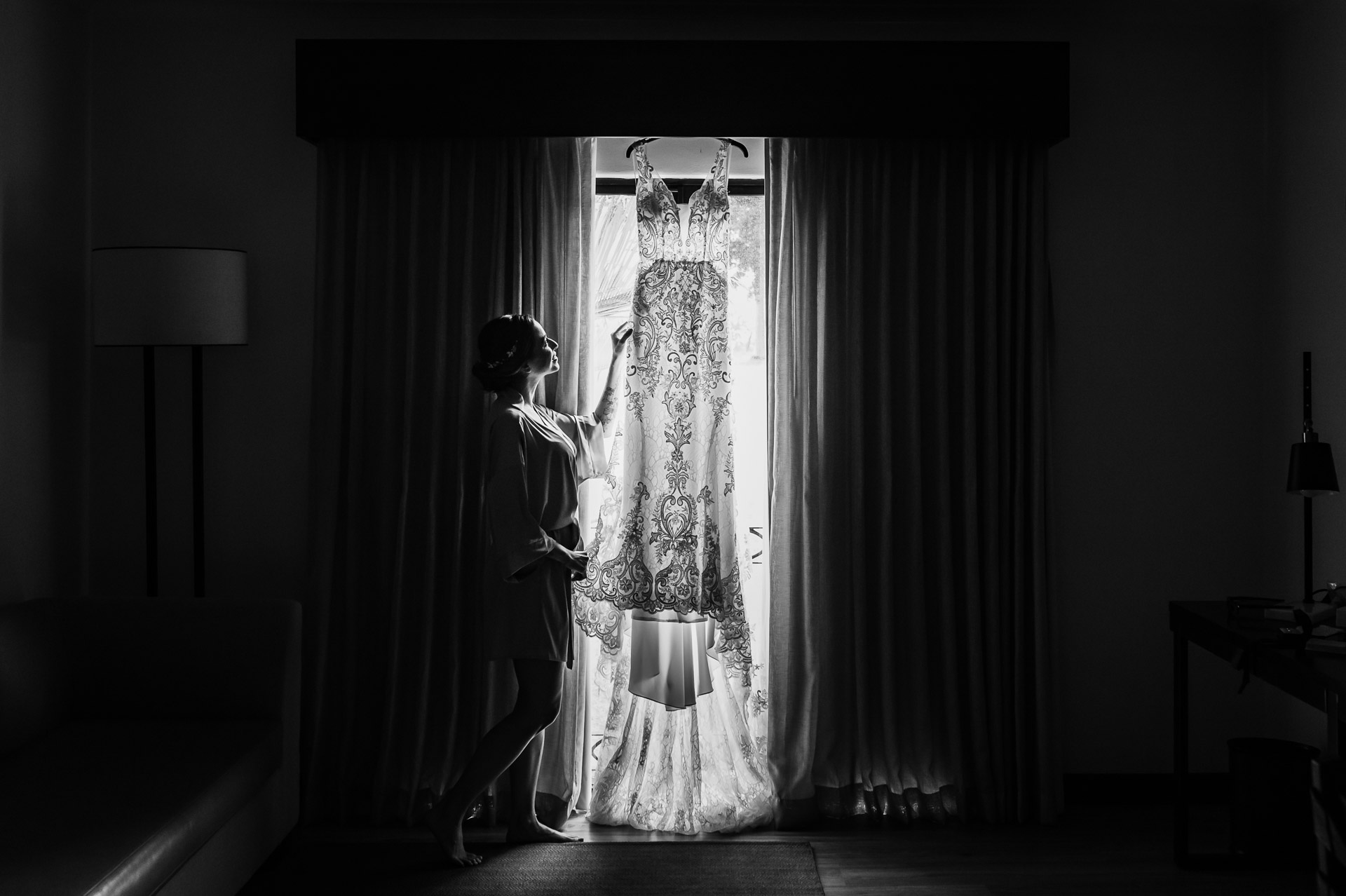 Wedding Venue Pictures in San Jose Costa Rica | The bride is taking a closer look at her beautiful dress
