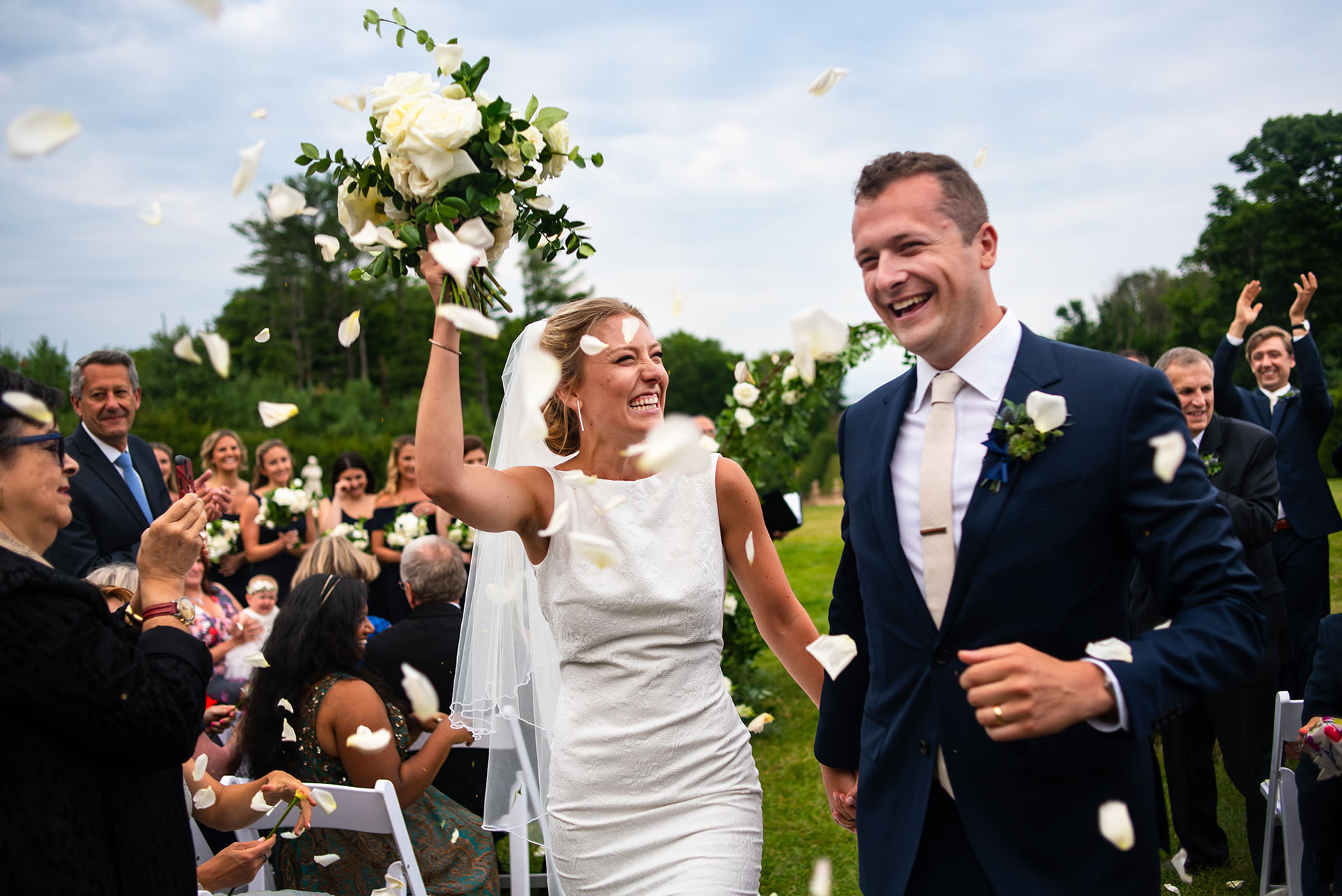 The Celebration Begins with flower petals for the bride and groom at the end of this outdoor wedding ceremony