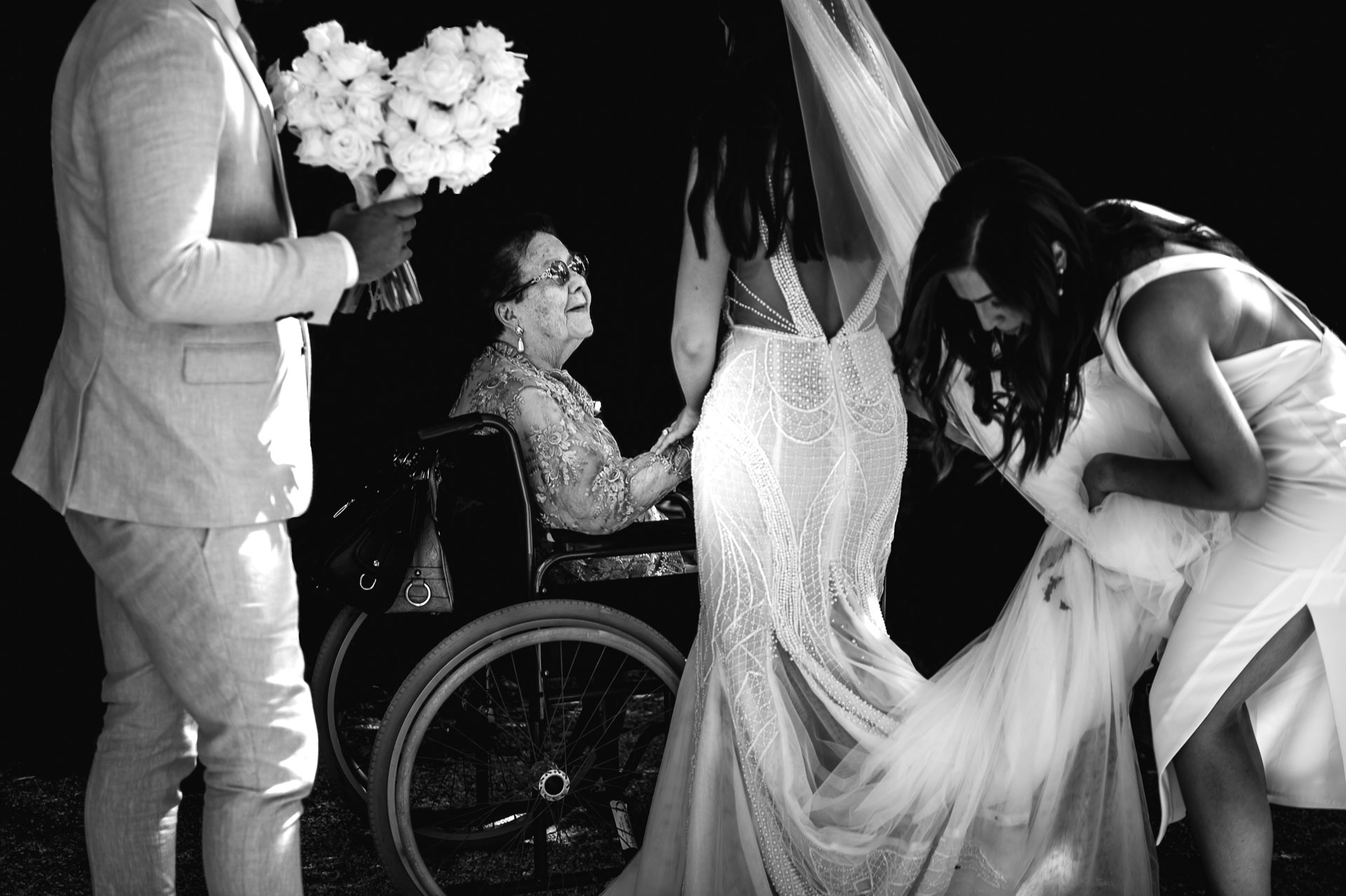 Wedding photograph of the bride holding and the hand of an elderly woman seated in her wheelchair