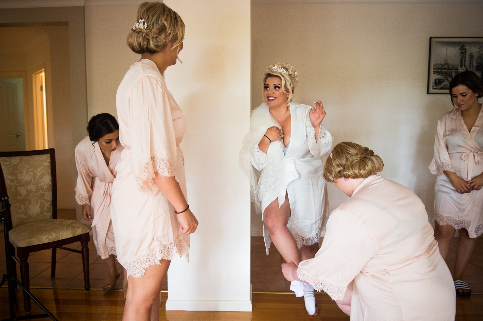 Photo of the bride as she is laughing with her bridesmaids and relatives while putting on socks before the wedding.