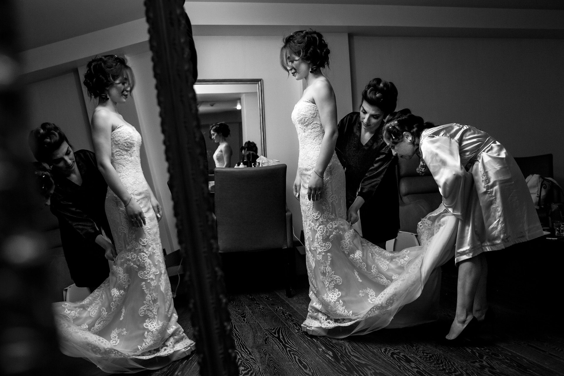 Wedding prep photography of the donning of the bridal gown.