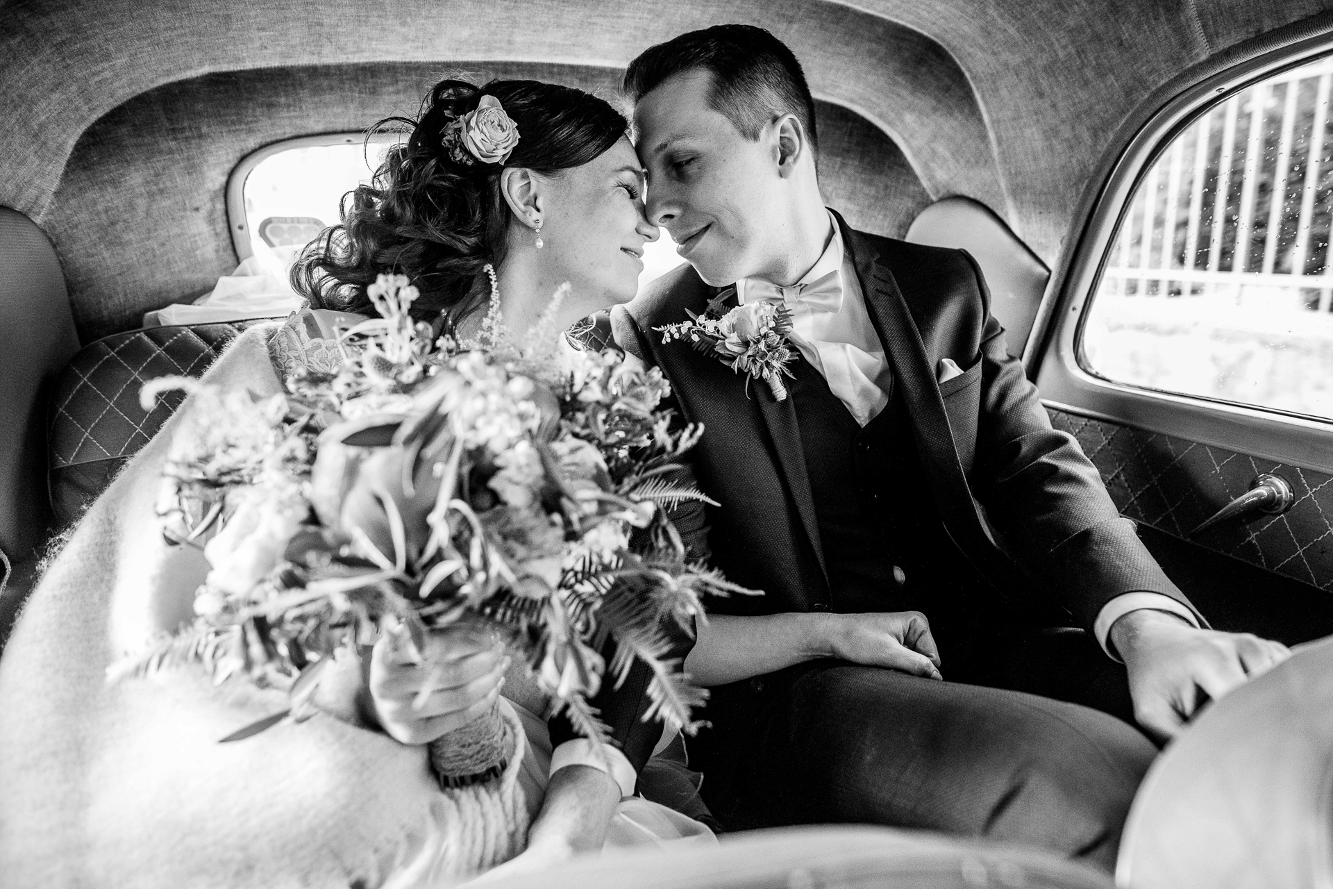 Black and White photo of the bride and groom having a quiet and intimate moment alone in the backseat of the car