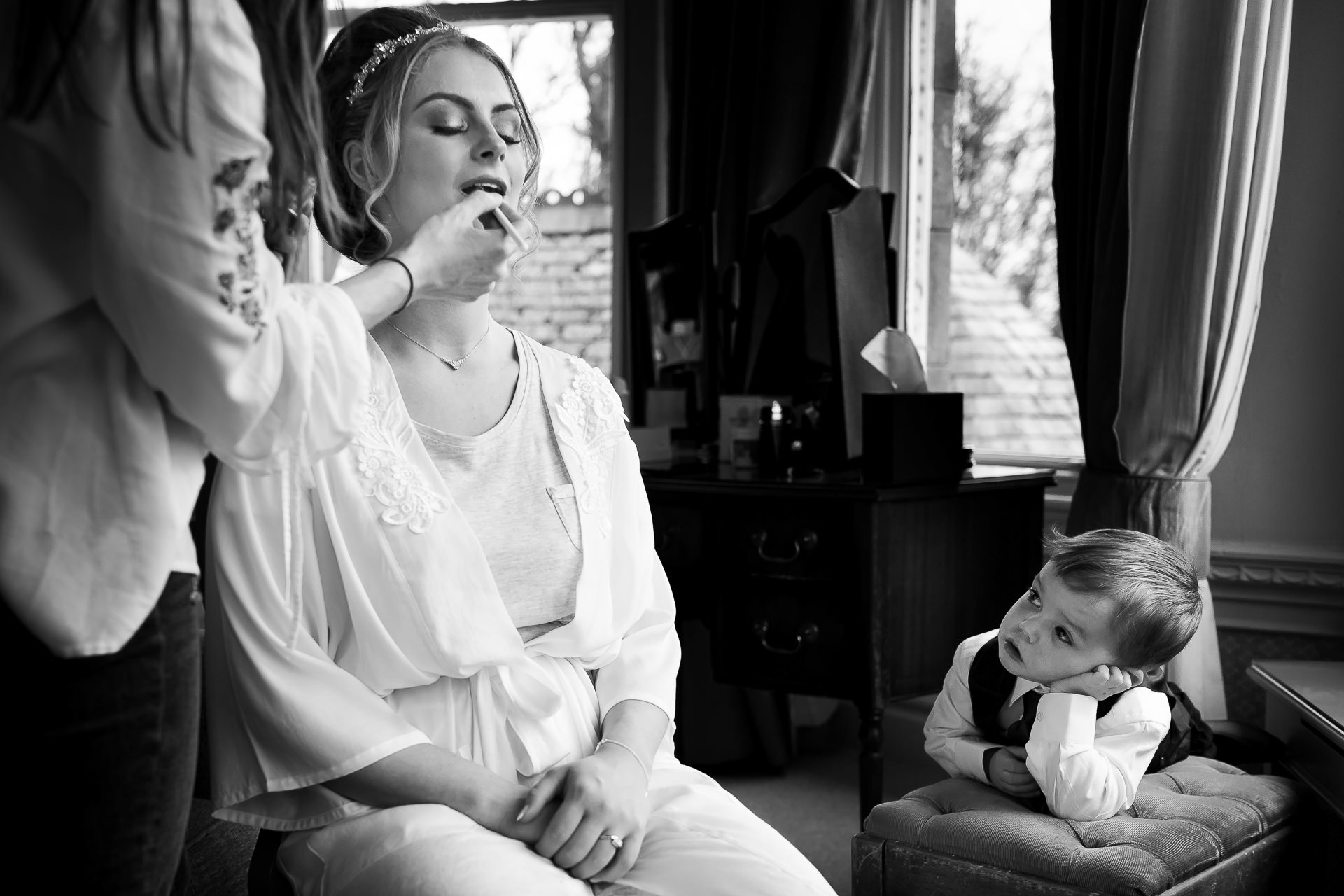 Black and white photo of a young boy watching as the bride gets her makeup done | Wedding Preparation Photographers