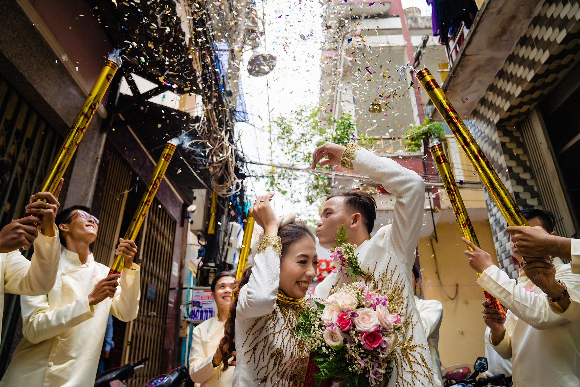 Photo of the bride and groom as the groomsmen fire confetti cannons around them by a wedding photographer.