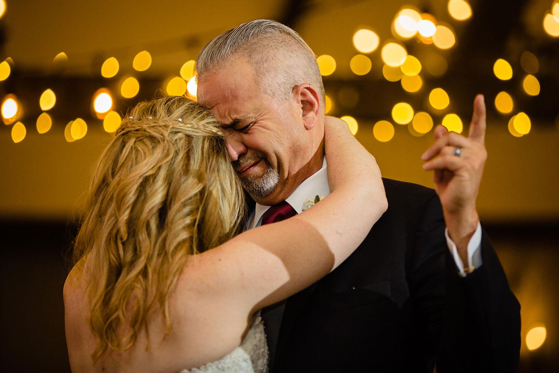 Huwelijksfotografie momenten met ouders. Foto van de vader die met zijn dochter danst. Ouders worden emotioneel op de bruiloft.
