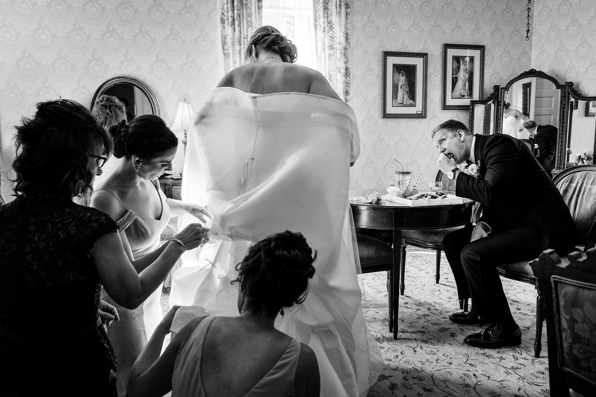 Fotografia di matrimonio di scena impegnativa per prepararsi | Immagine dello sposo che si diverte come la sposa, le sue damigelle e sua madre provano a farla impazzire per l'ora dell'aperitivo