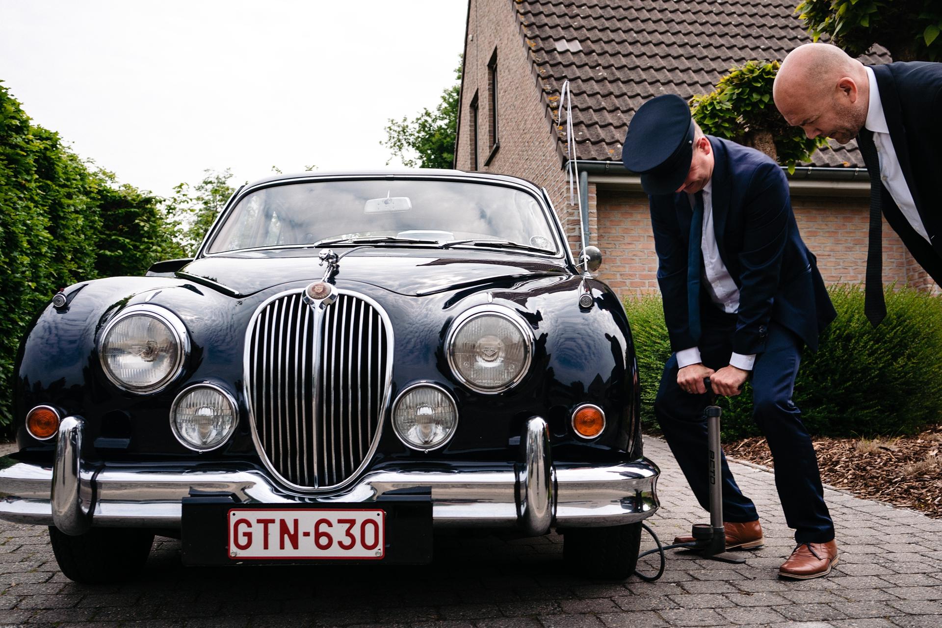 Der Hochzeitsfotograf hat dieses Bild des Fahrers des feierlichen Wagens aufgenommen, der einen platten Reifen hat, kurz bevor das Paar gehen muss - stressige Momente für Hochzeitsfotos