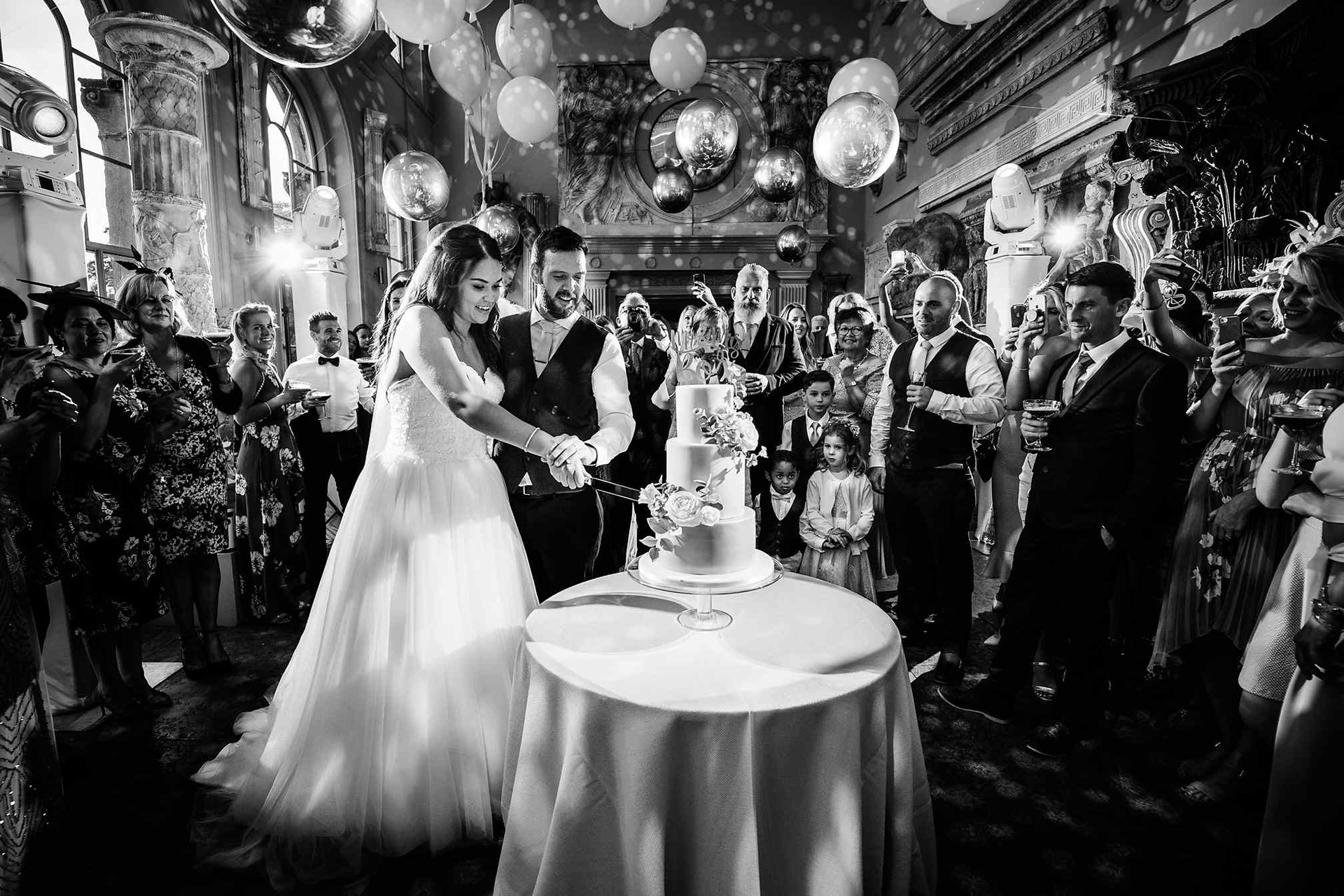 Wedding photography showing the bride and groom cutting the cake