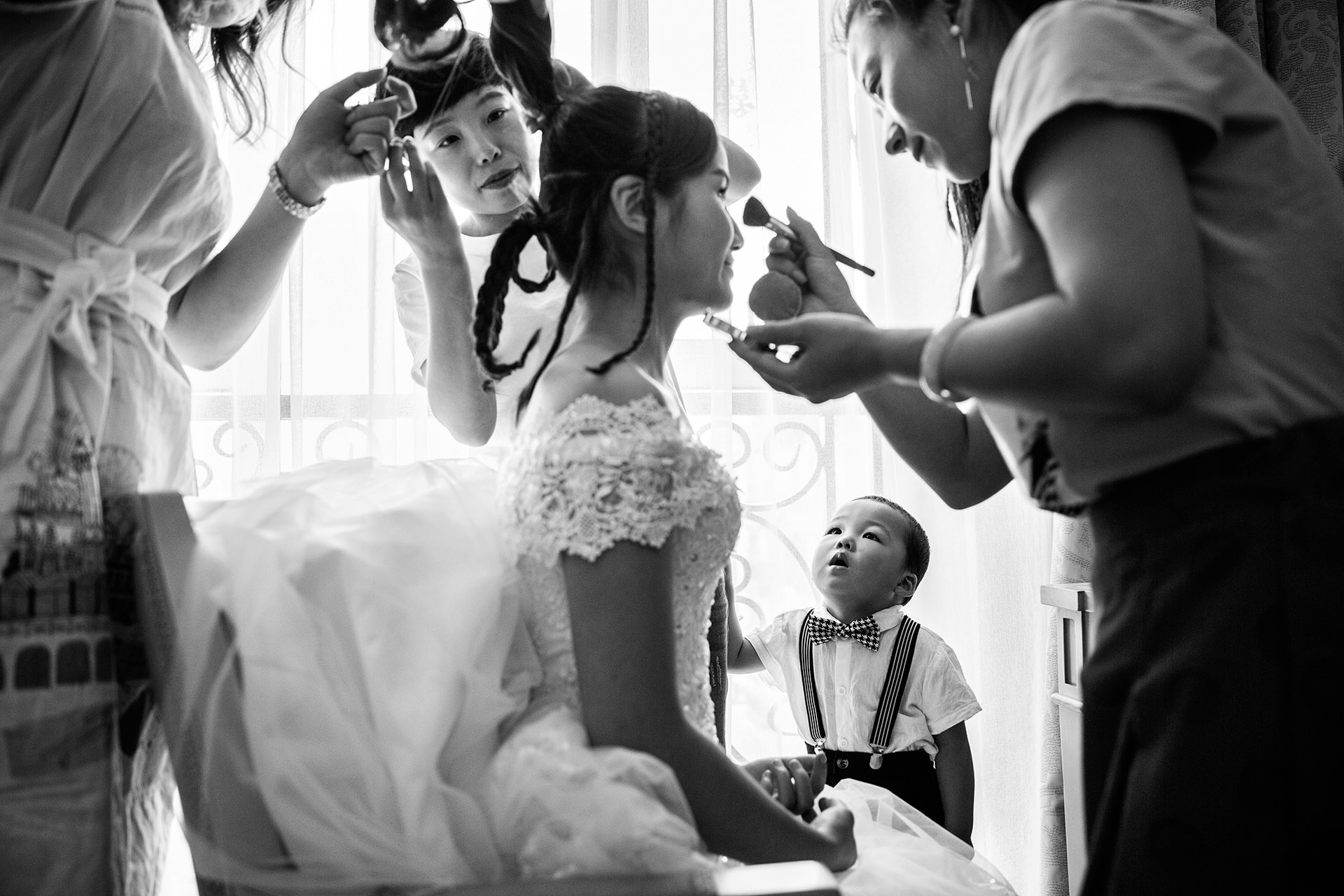 Bridesmaids and a little boy watch as the bride gets her makeup done in a busy room in this black and white photo