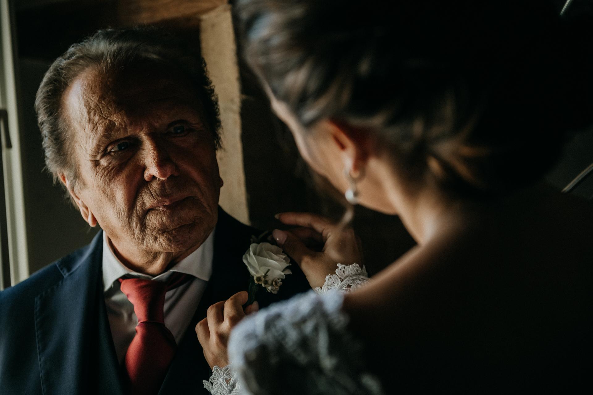 Trouwfoto van ouders die de emotie van de vader tonen met zijn dochter, de bruid terwijl ze zijn bloem op zijn jas speldt
