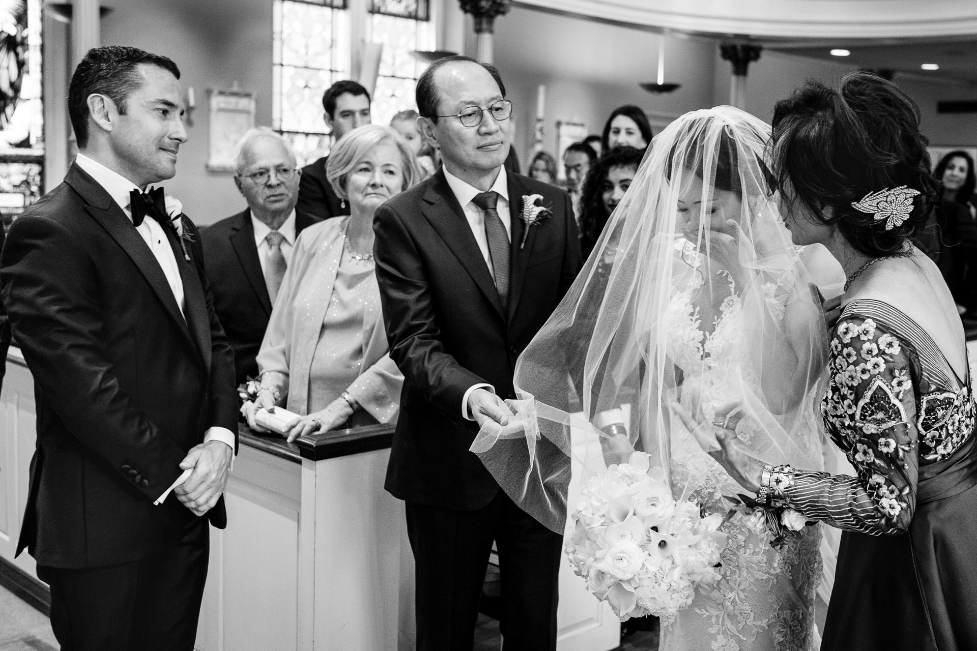 Trouwdagfotografie met de ouders. Afbeelding van de moeder en vader van de bruid die haar sluier verwijderen terwijl de bruidegom toekijkt.