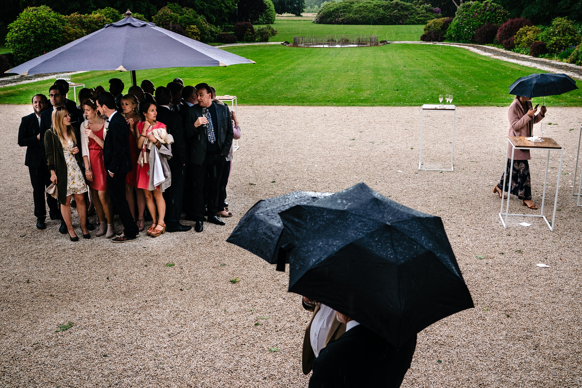 Wedding Photos when it rains | Surprise rainfall at this wedding reception had the guests taking shelter under umbrellas.
