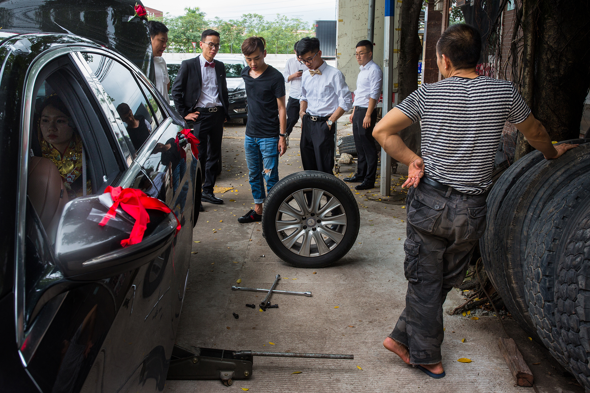 Wedding Photojournalism - Groomsmen take a car to a mechanic to change a tire in this photo taken by an award-winning wedding photojournalist.