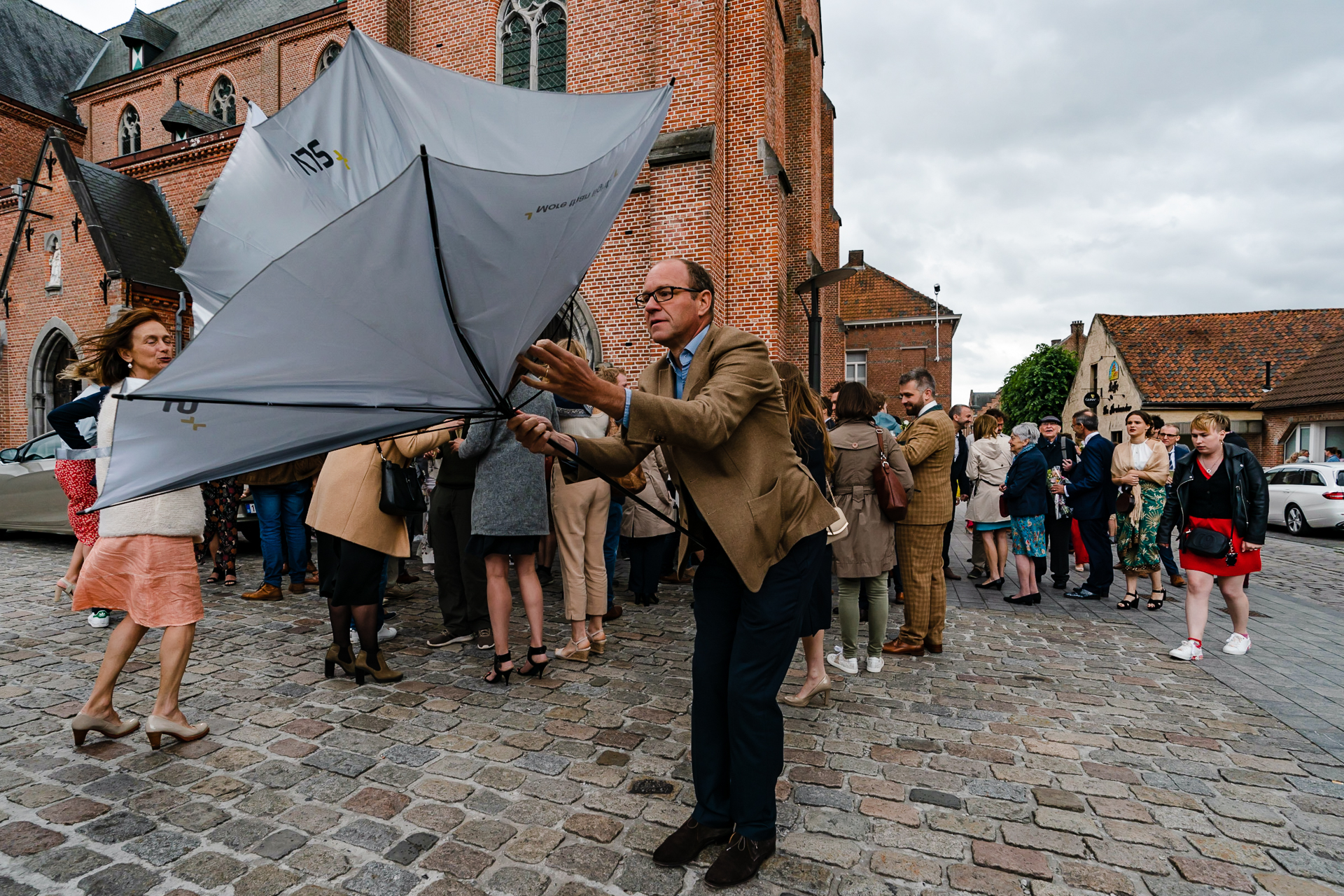 Wedding Day Rain Photography | Guests battle the wind and water with umbrellas at the reception.