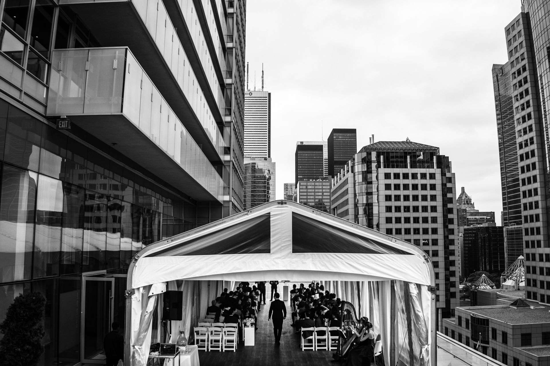 Urban, city tent over the groom wakling into the ceremony location - Tent wedding photography