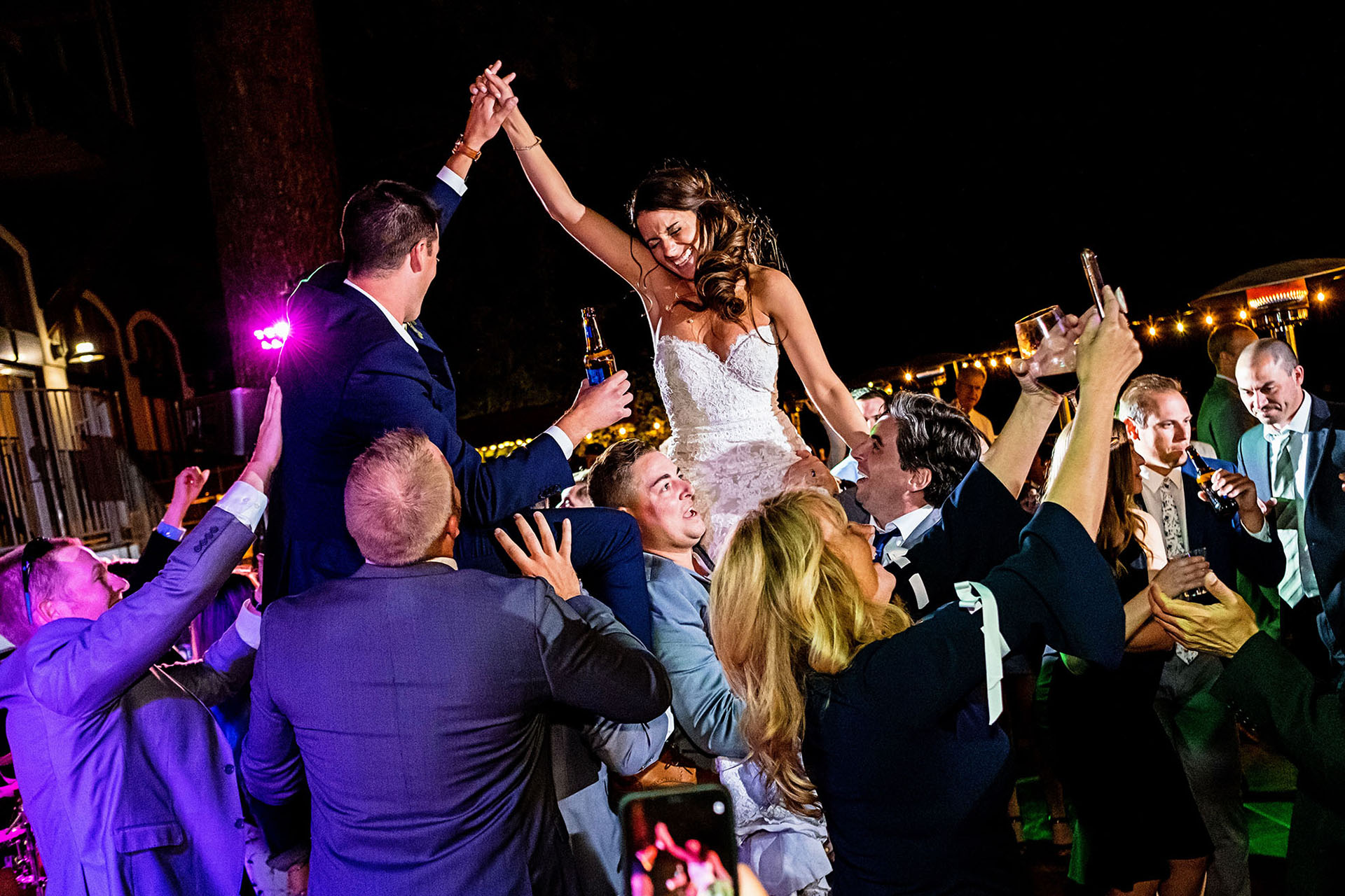 Wedding Photos at Reception - Bride and Groom are lifted up in celebration