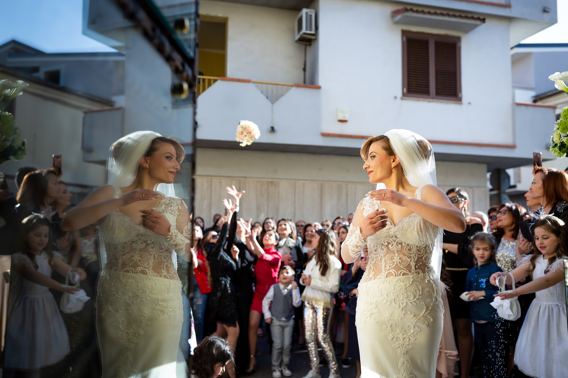The Best Wedding Photojournalism - The bride turns toward her reflection as she tosses her bouquet over her shoulder in this wedding photo.