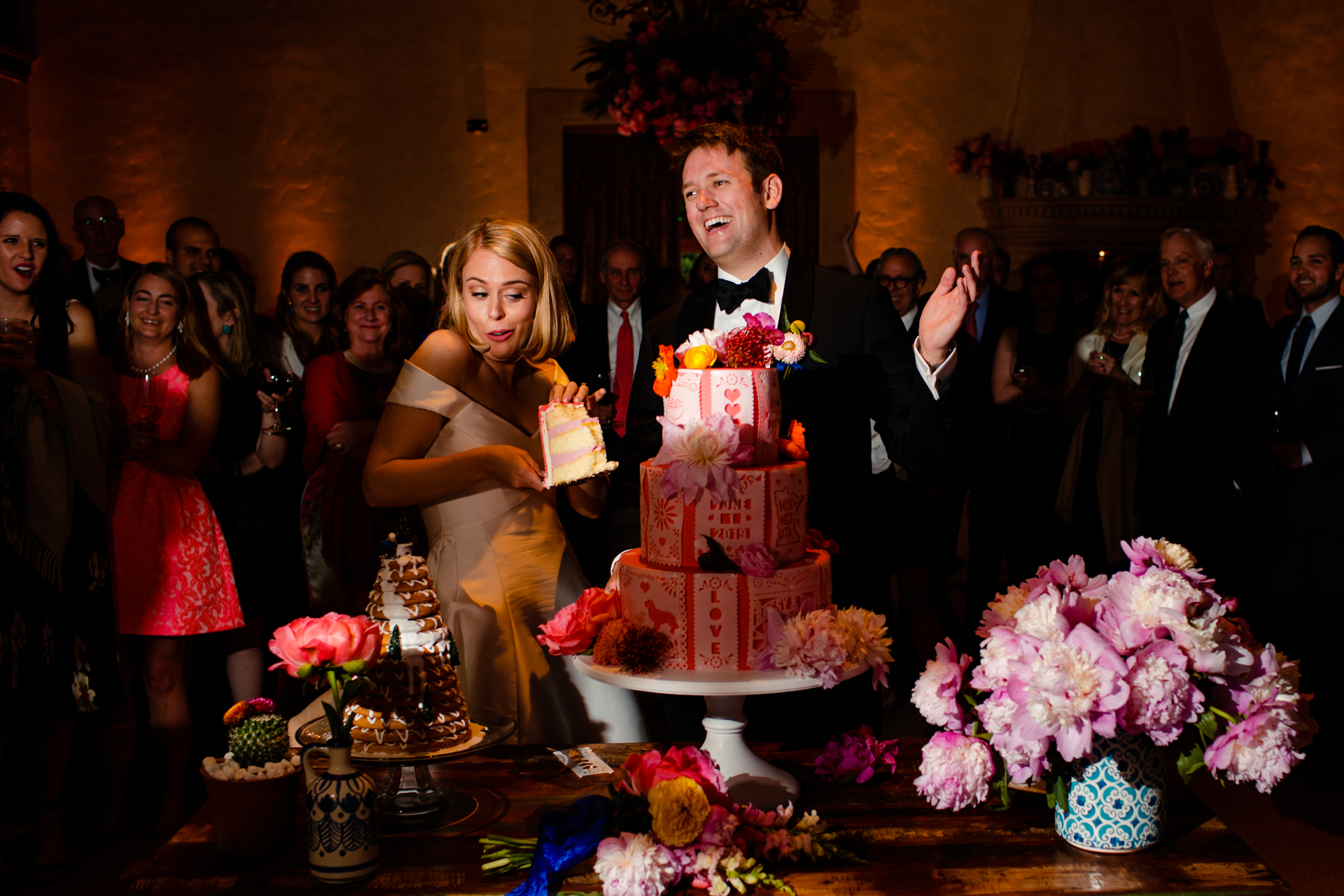 Cake cutting photograph with the bride and groom deciding if they should smash or not smash the cake.