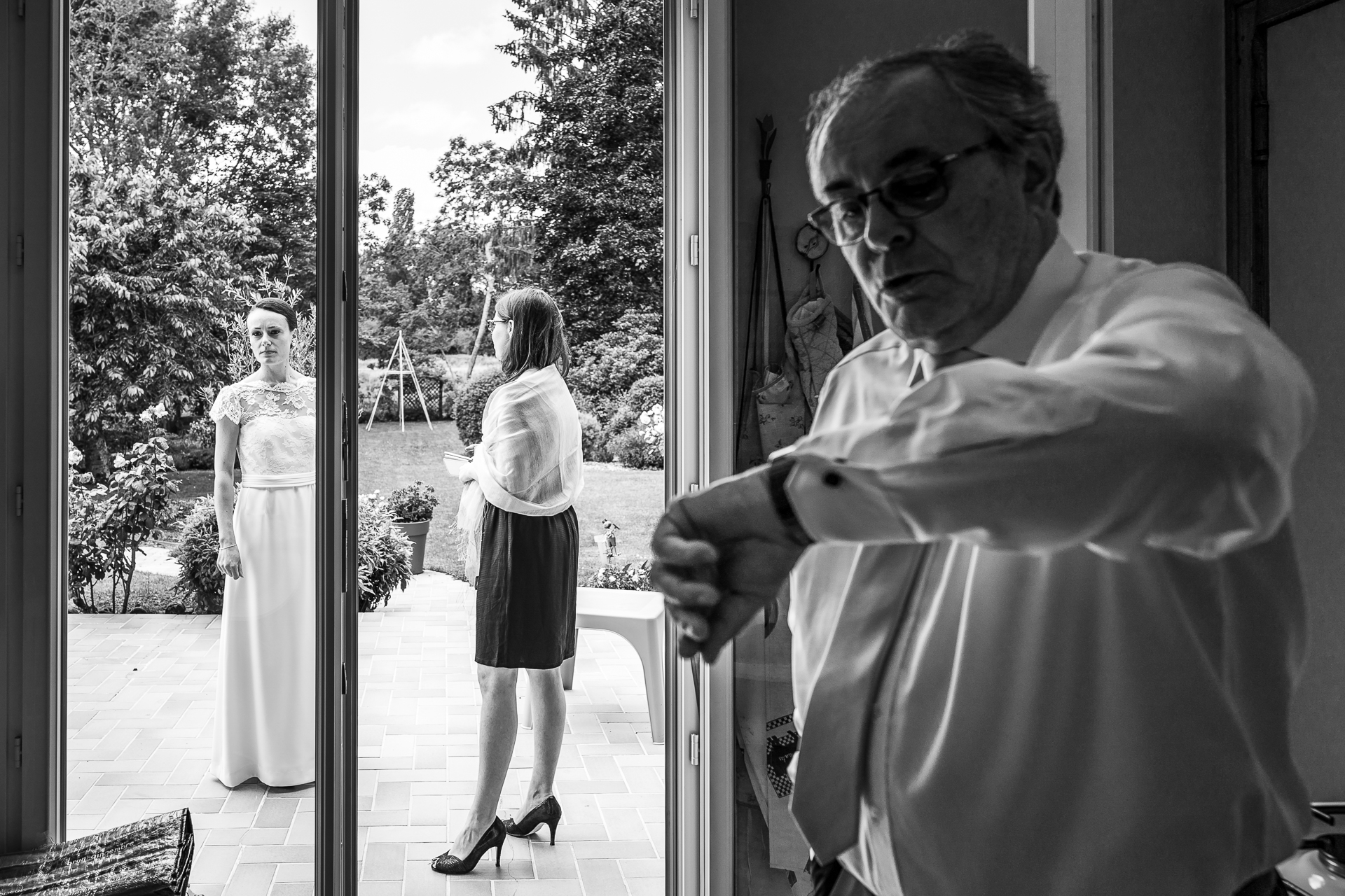 Ein Mann schaut auf die Uhr vor der Zeremonie in Checy auf diesem Schwarzweiß-Hochzeitsfoto