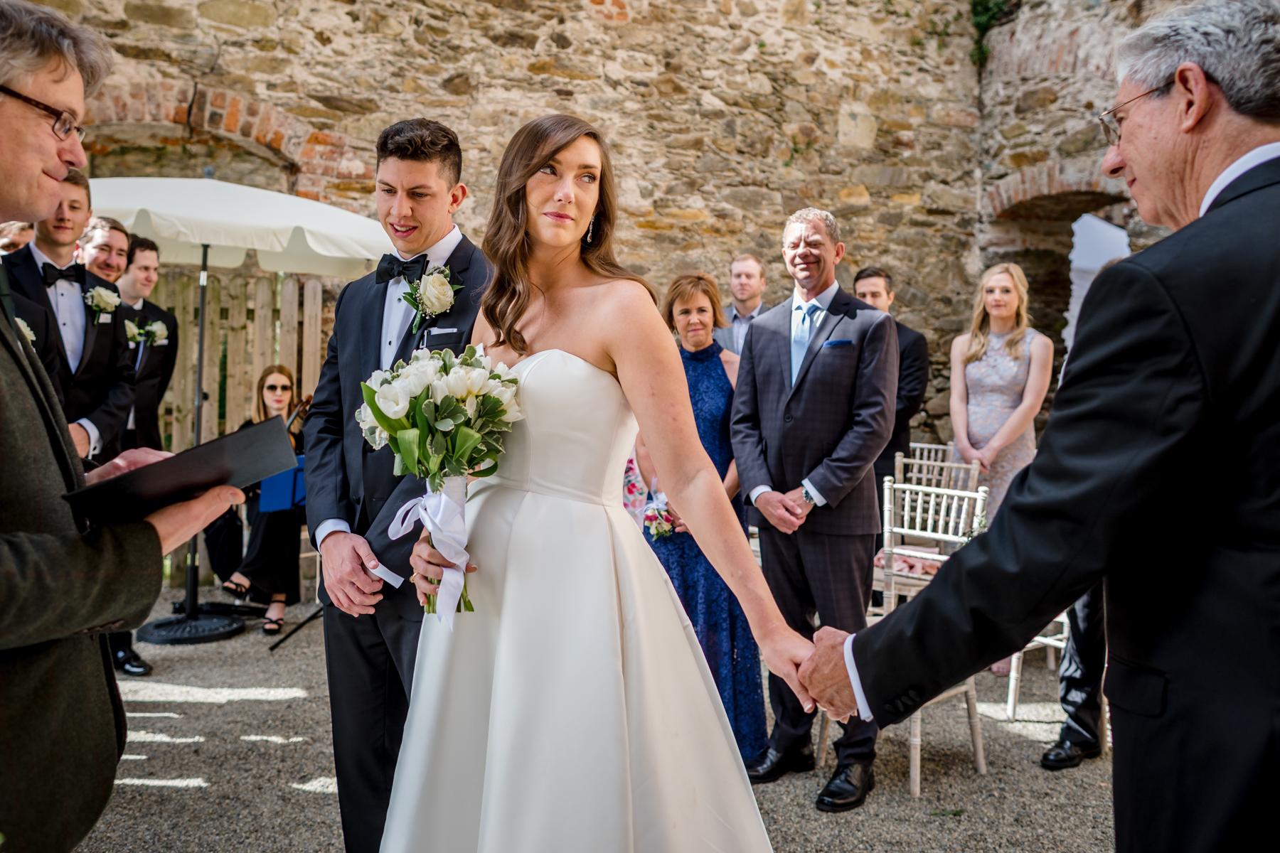 Hochzeitsfotografie von Eltern - Zeremonienbild, welches die Übergabe durch den Vater der Braut an den Bräutigam zeigt