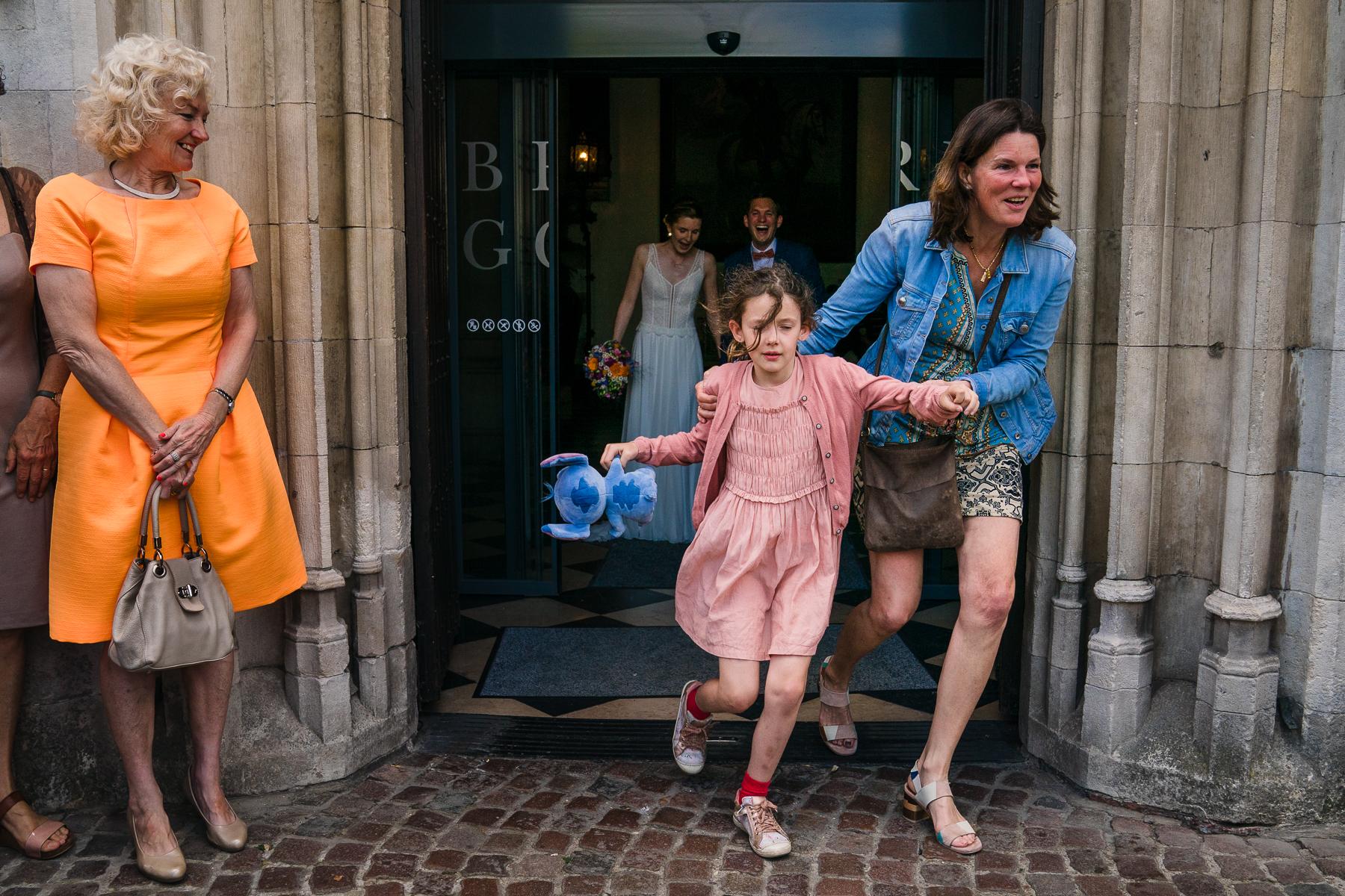 Auf diesem Hochzeitsfoto rennen ein kleines Mädchen und ihre Mutter aus dem Rathaus