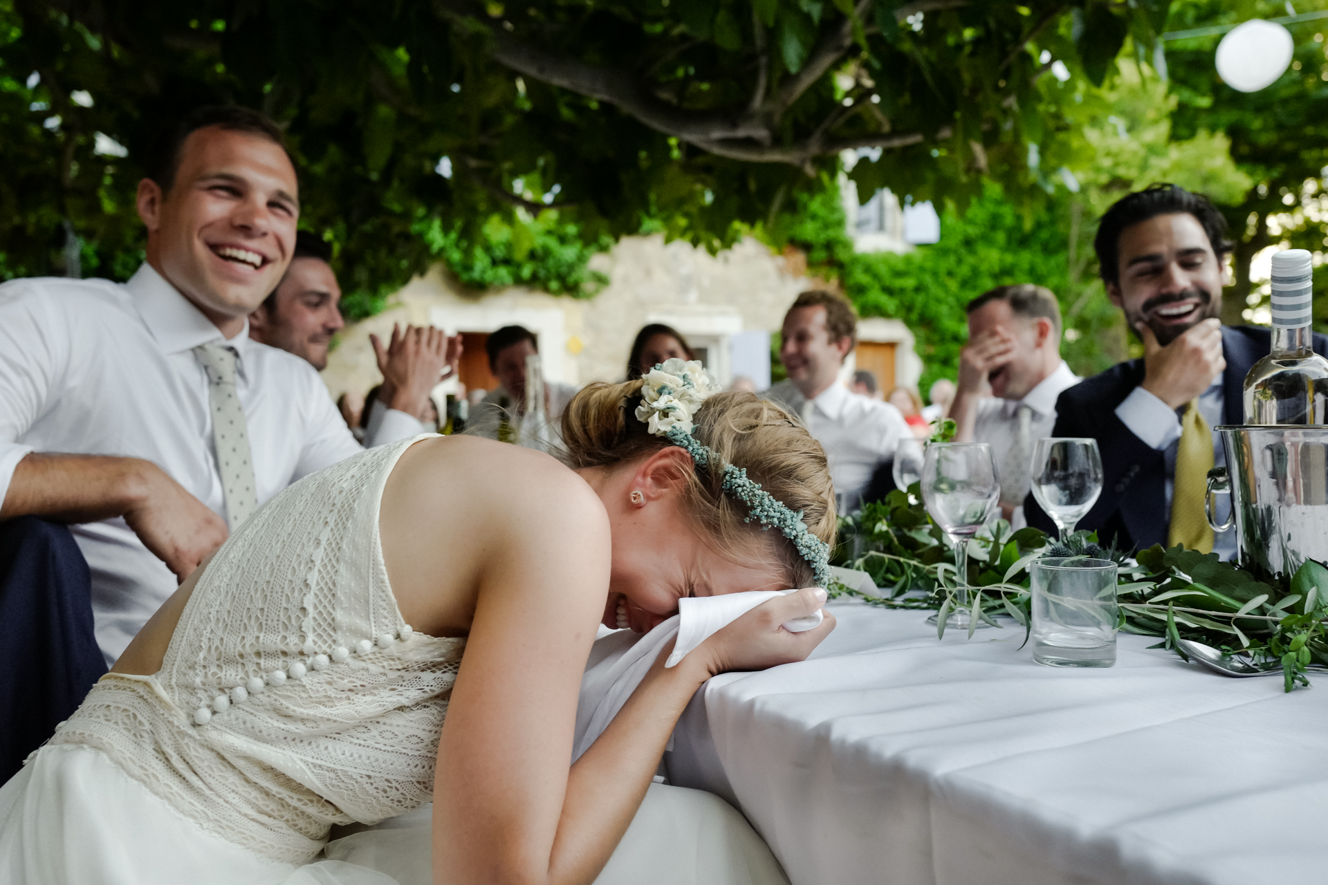 The guests and bride cannot stop laughing during a funny speech at her wedding reception. Photography of reactions on wedding day.