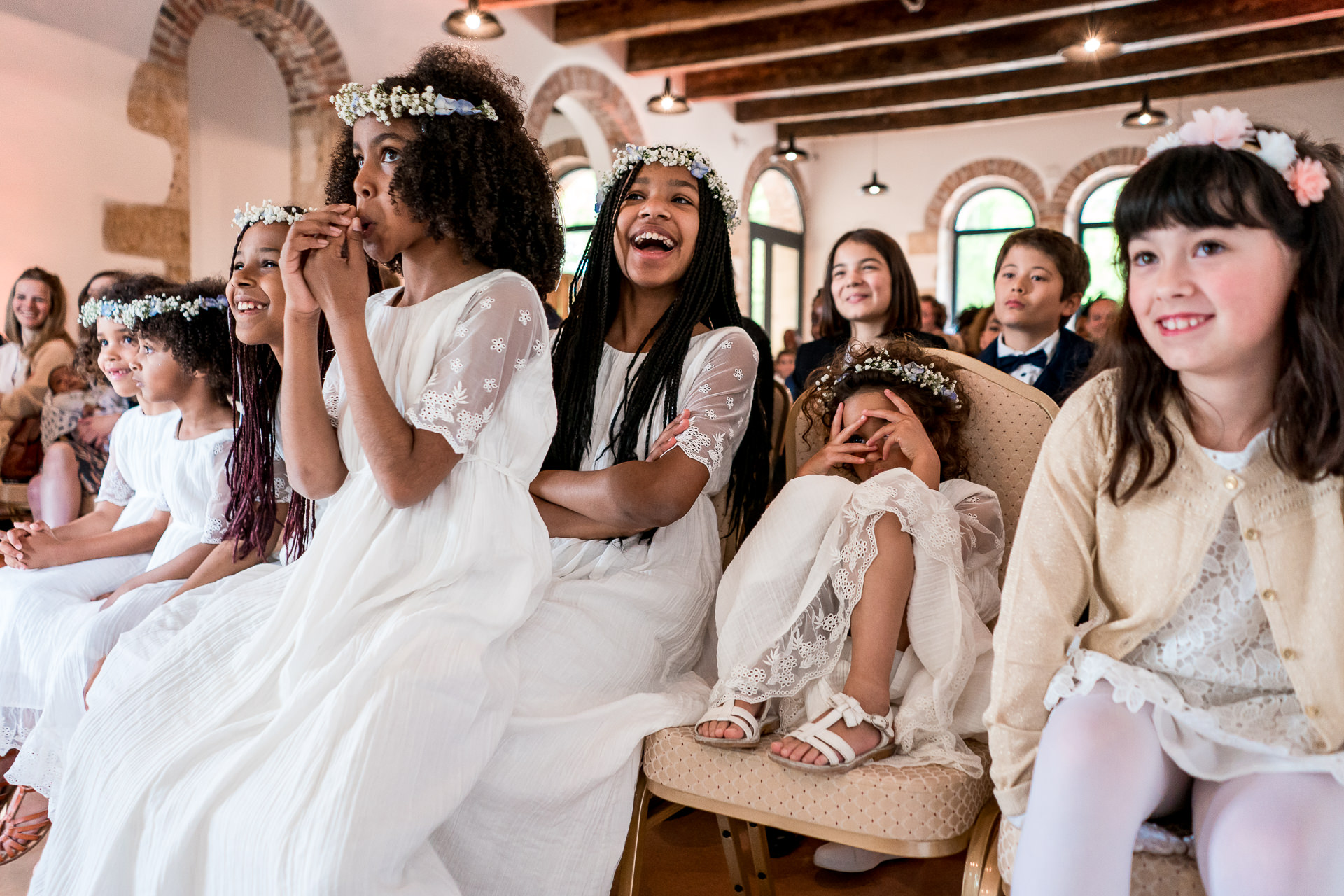 Wedding photography of girls in dresses laughing during ceremony