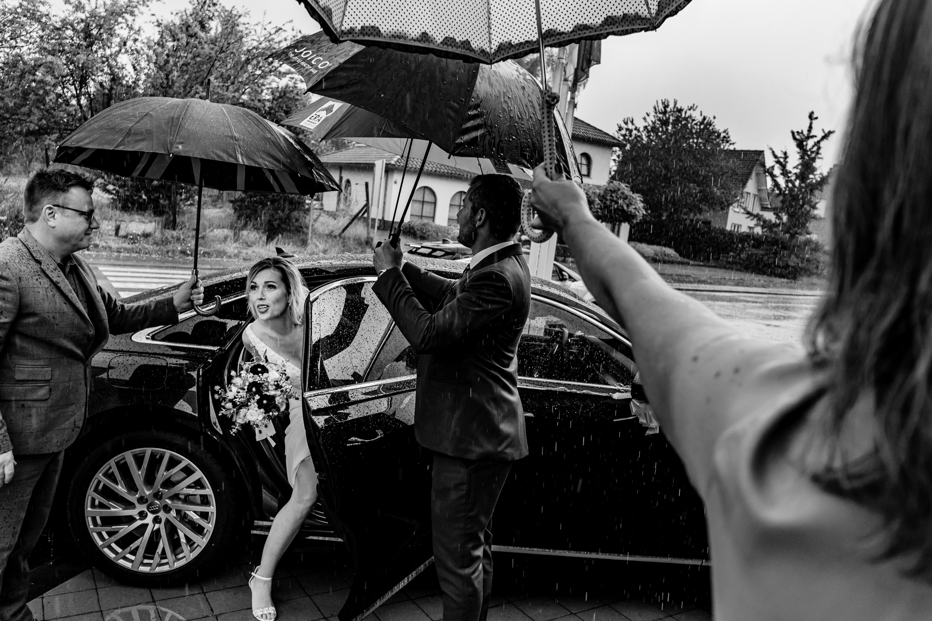Guests hold umbrellas over the bride as she exits her vehicle | Photography in the Rain on Wedding Day