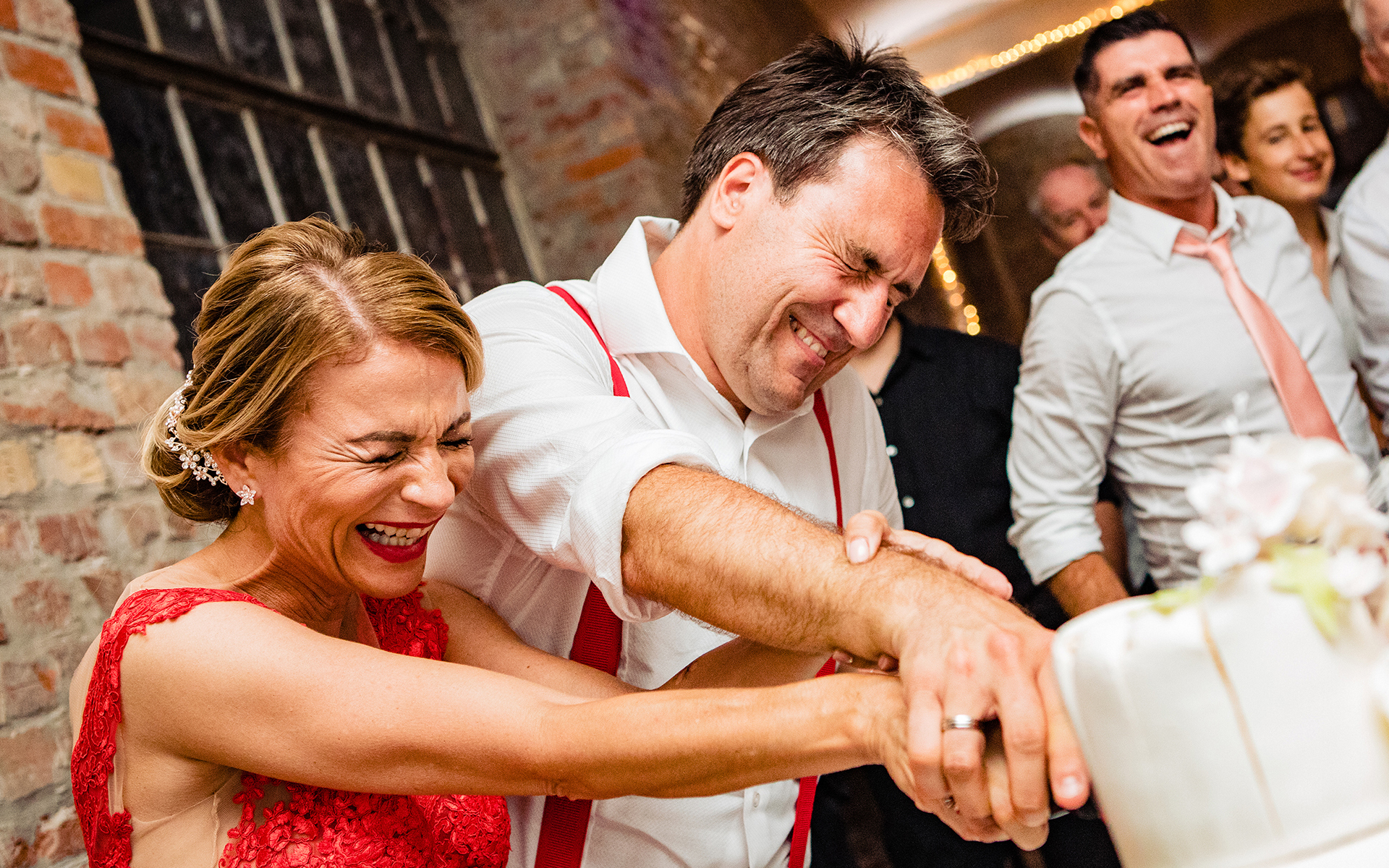 Bride and the groom are cutting the cake in this wedding photo under extreme difficulty.