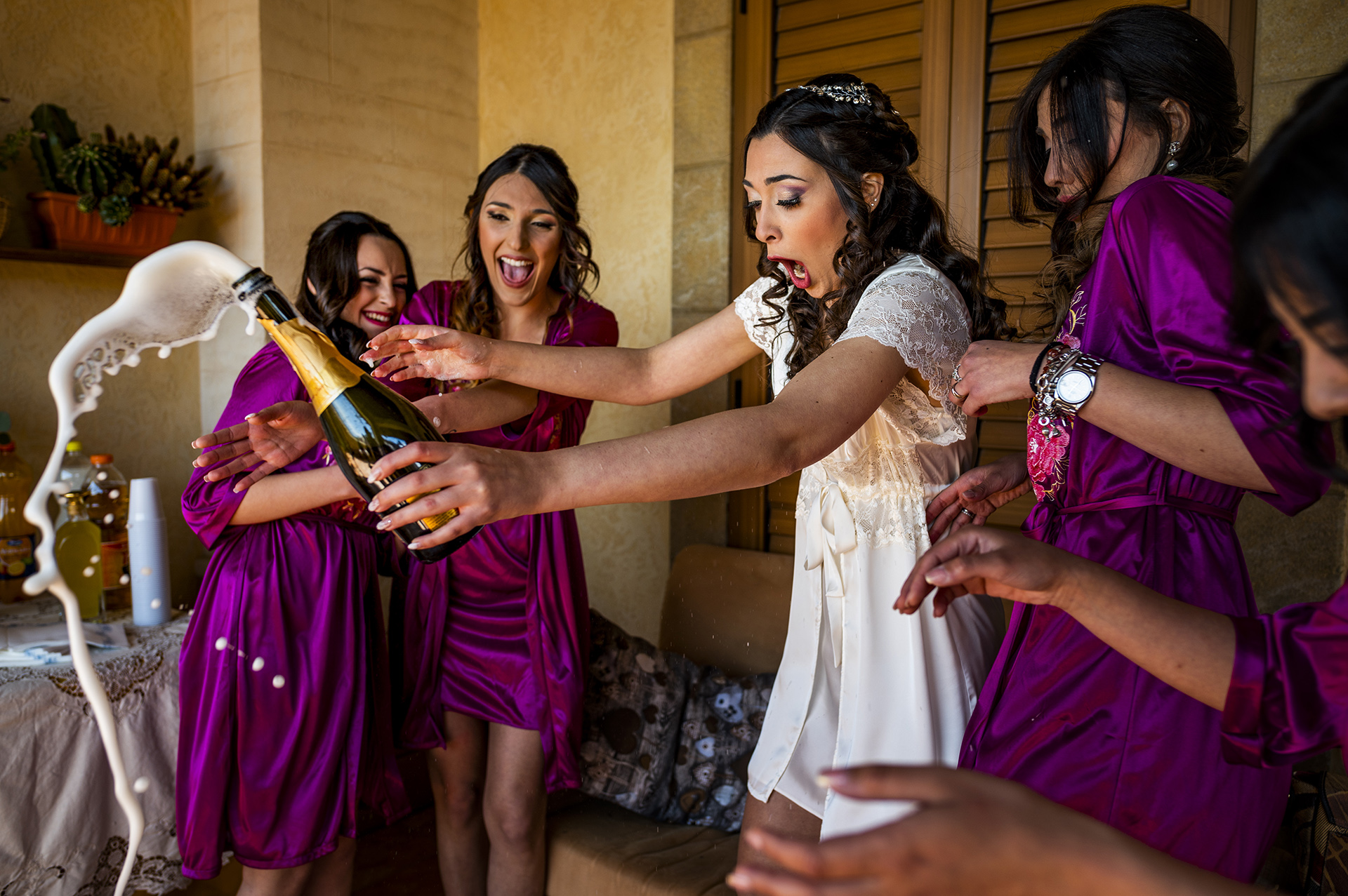 The bride and bridal party are shocked as the bottle of champagne pops open while they are getting ready for the wedding.