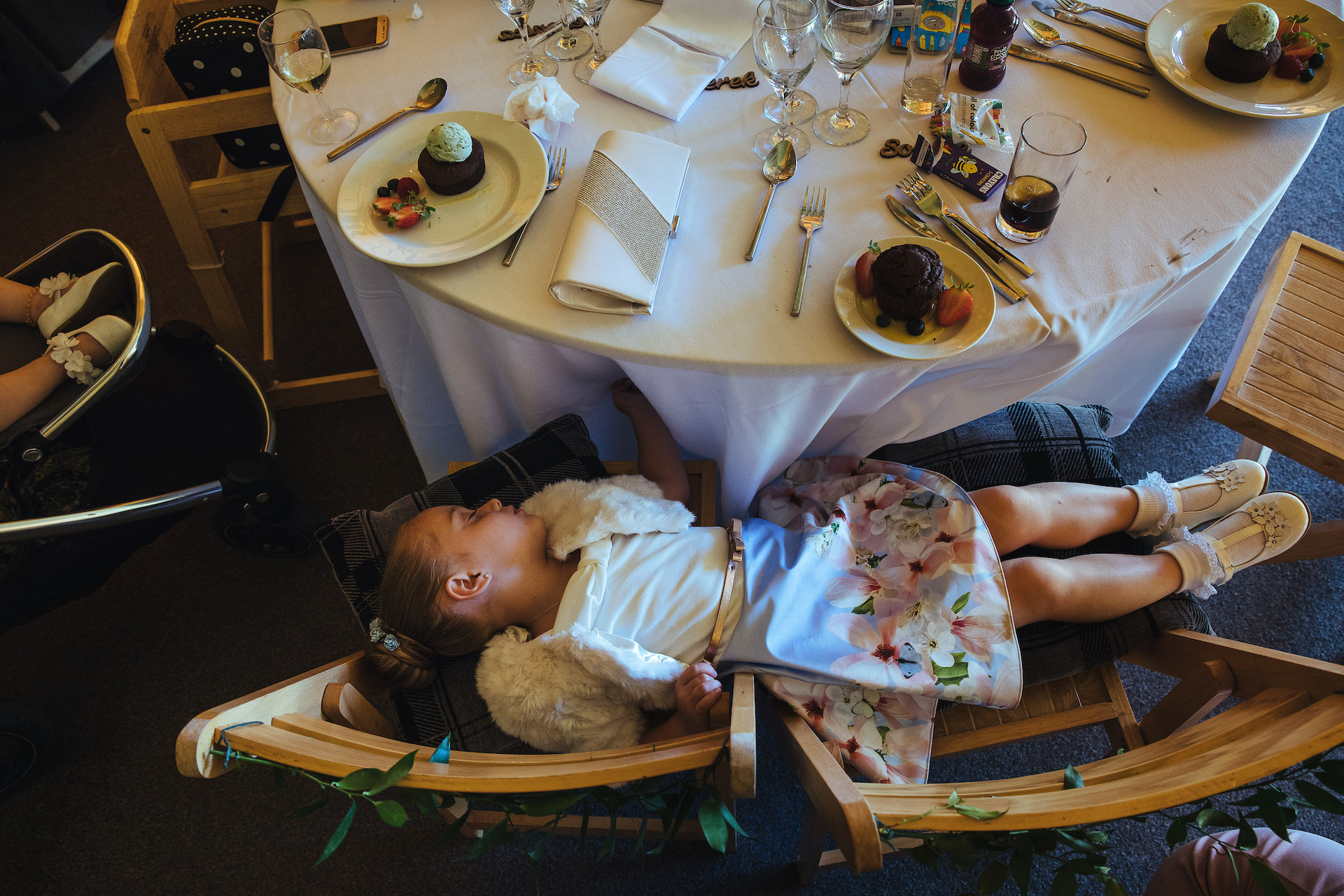 Away from the main wedding action, a photo of a young flowergirl asleep at the table