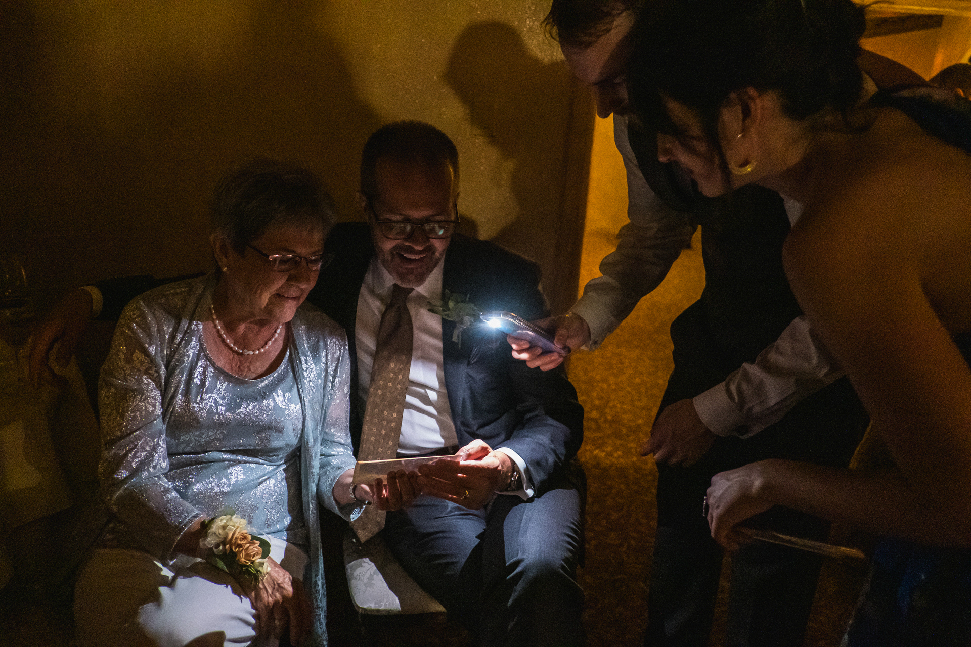 Wedding photography showing the father and grandmother of the bride looking at a photo together in the dark as wedding guests light it with a cellphone light.