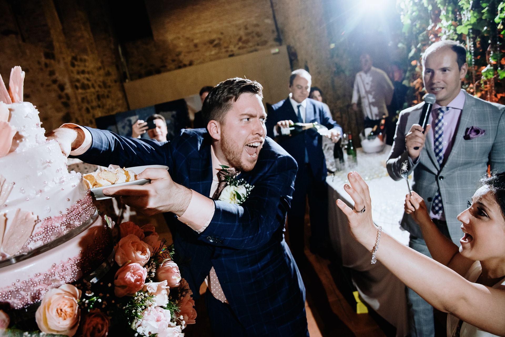 Humorous image of the groom at the wedding reception reaching into the cake bare-handed as he thinks about smashing it.