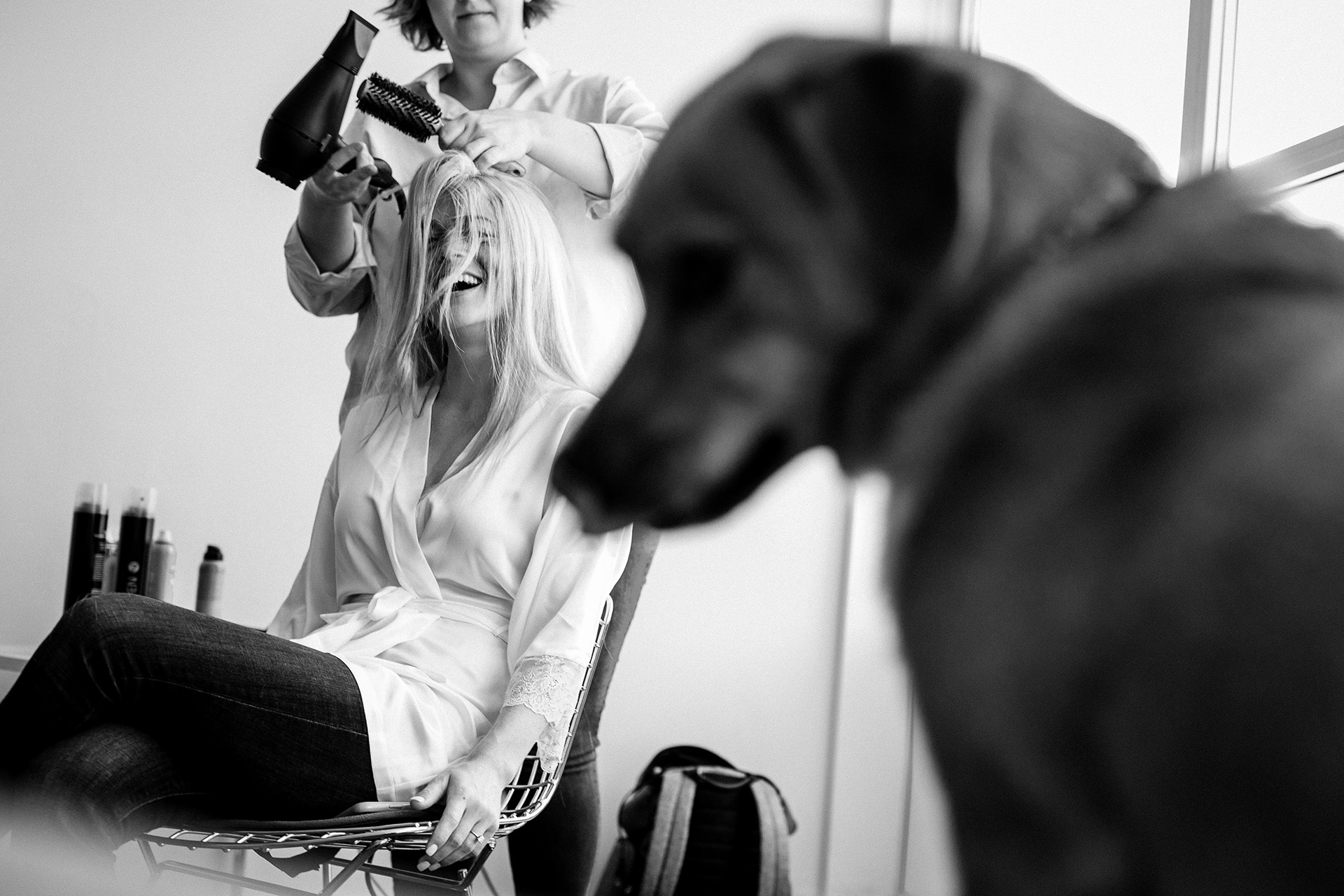 Memorable moments during getting ready photo session | the bride laughing with her dog in the foreground.