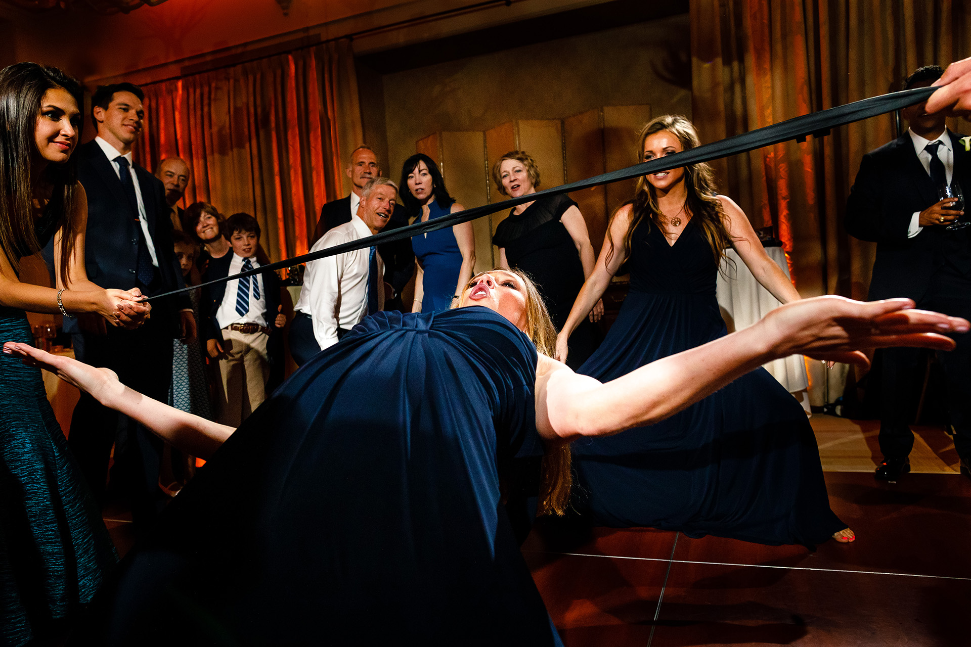 wedding photojournalist captured woman doing limbo at the reception party