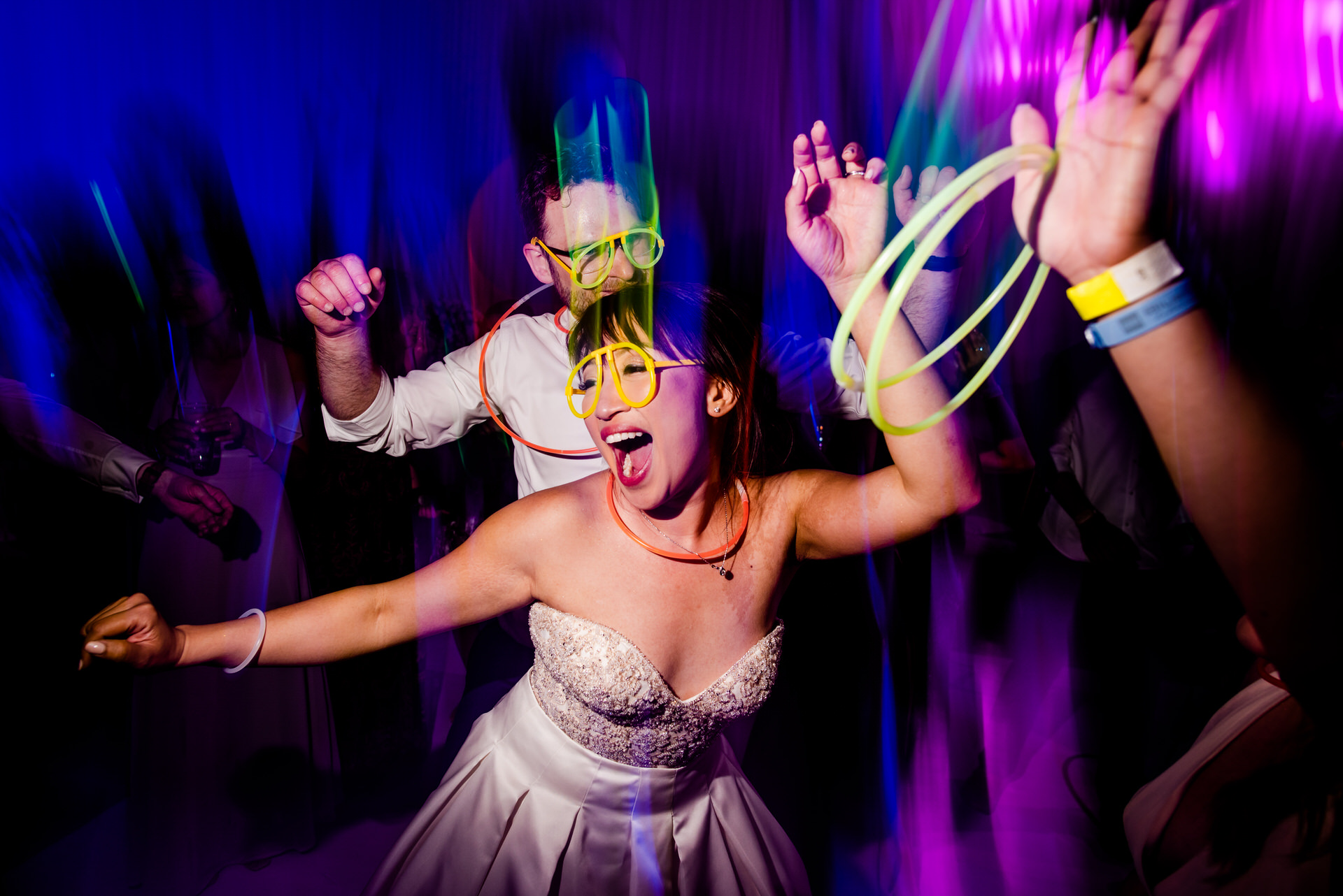 The wedding photographers camera shutter speed picks up motion and the moment freezes by the flash on the dance floor.