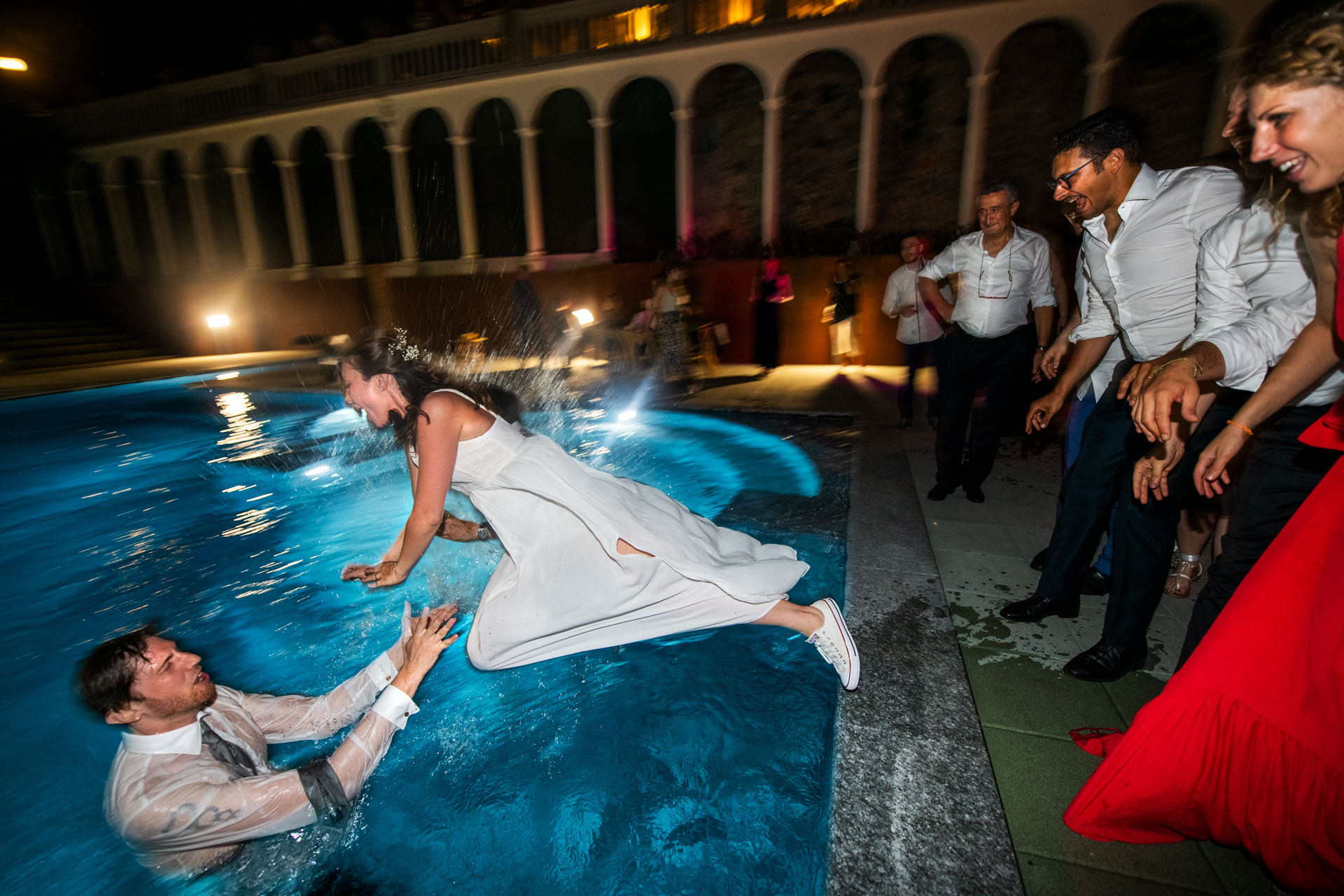 Photography of the moment of the bride's flight in the pool with the groom at the wedding reception