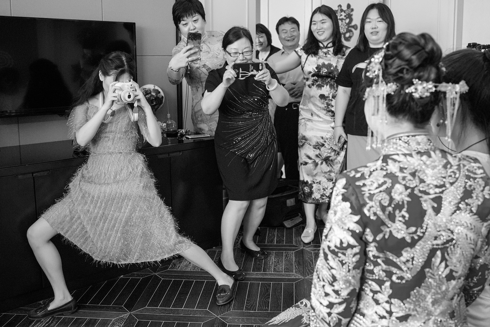 A black and white wedding photojournalism image of bride having her picture taken by a friend