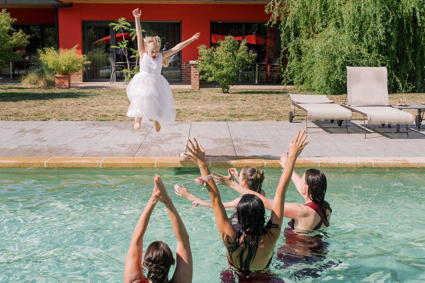 Kids at the wedding having fun jumping into the pool. Photo of flowergirl in white dress.