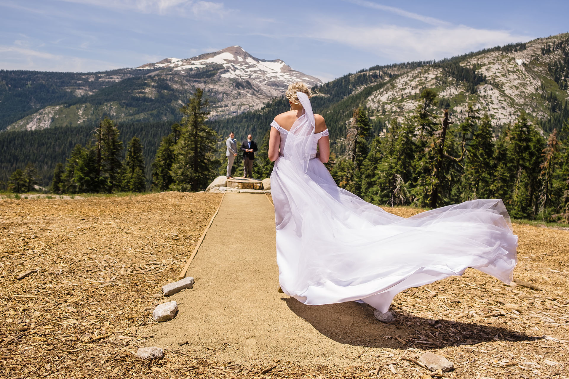 Clean background in this photo of the bride walking into her mountain ceremony.