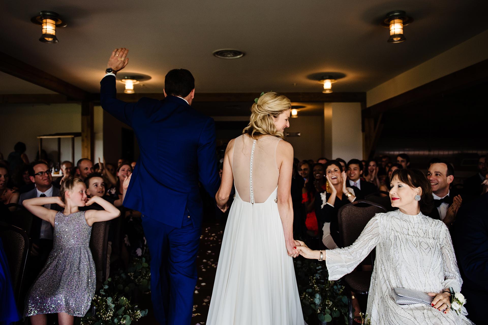 Ouders Huwelijksfotografie | De bruid geeft een kneepje in de hand van haar moeder terwijl ze zich terugtrekt van de ceremonie met haar nieuwe echtgenoot.