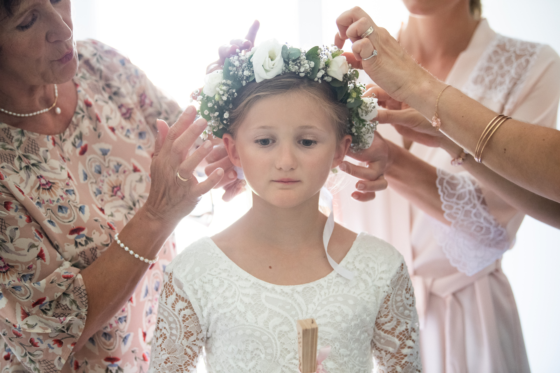 Photo of getting ready of young flower girl child with flowers in her hair
